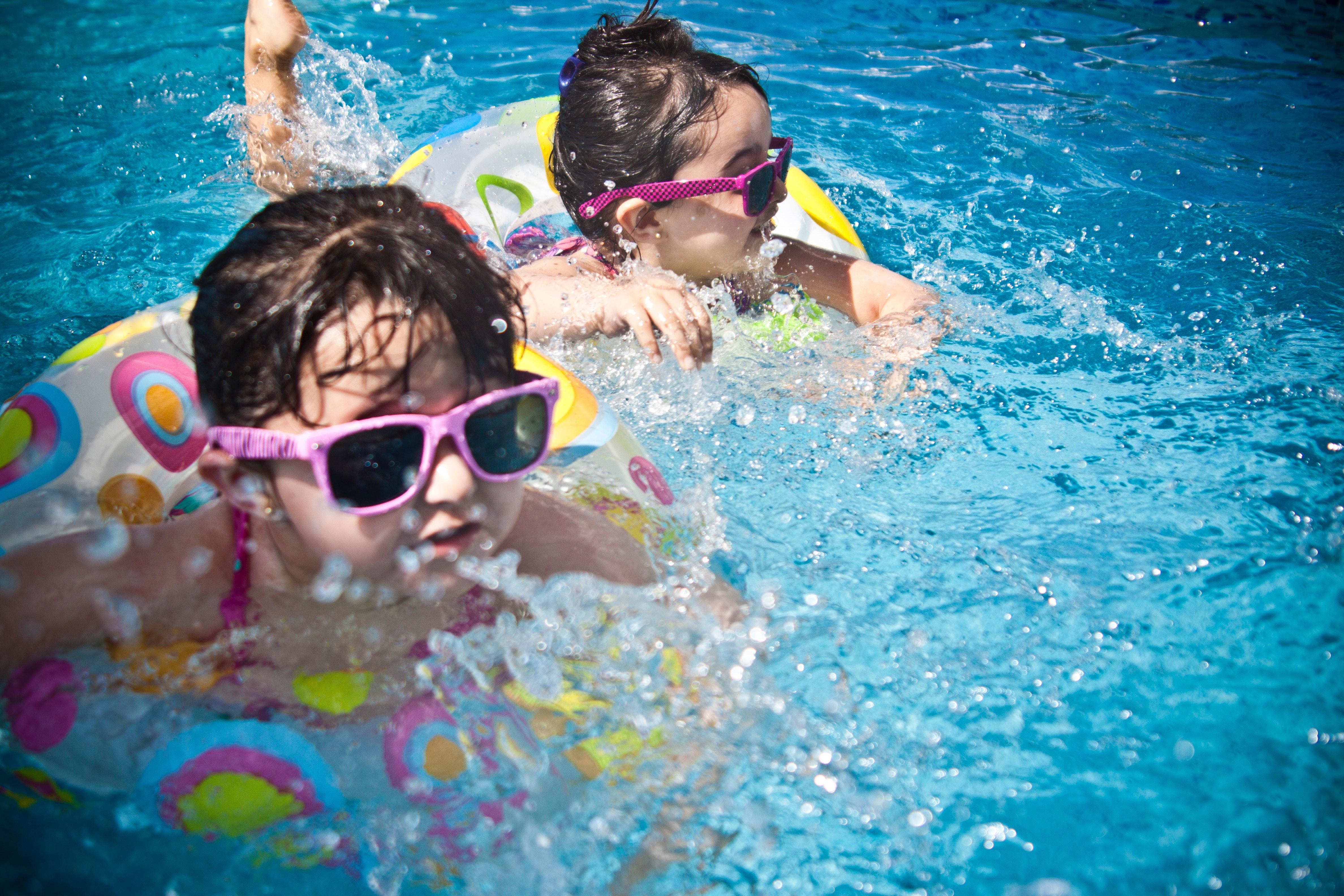 2 girl's swimming during daytime photo