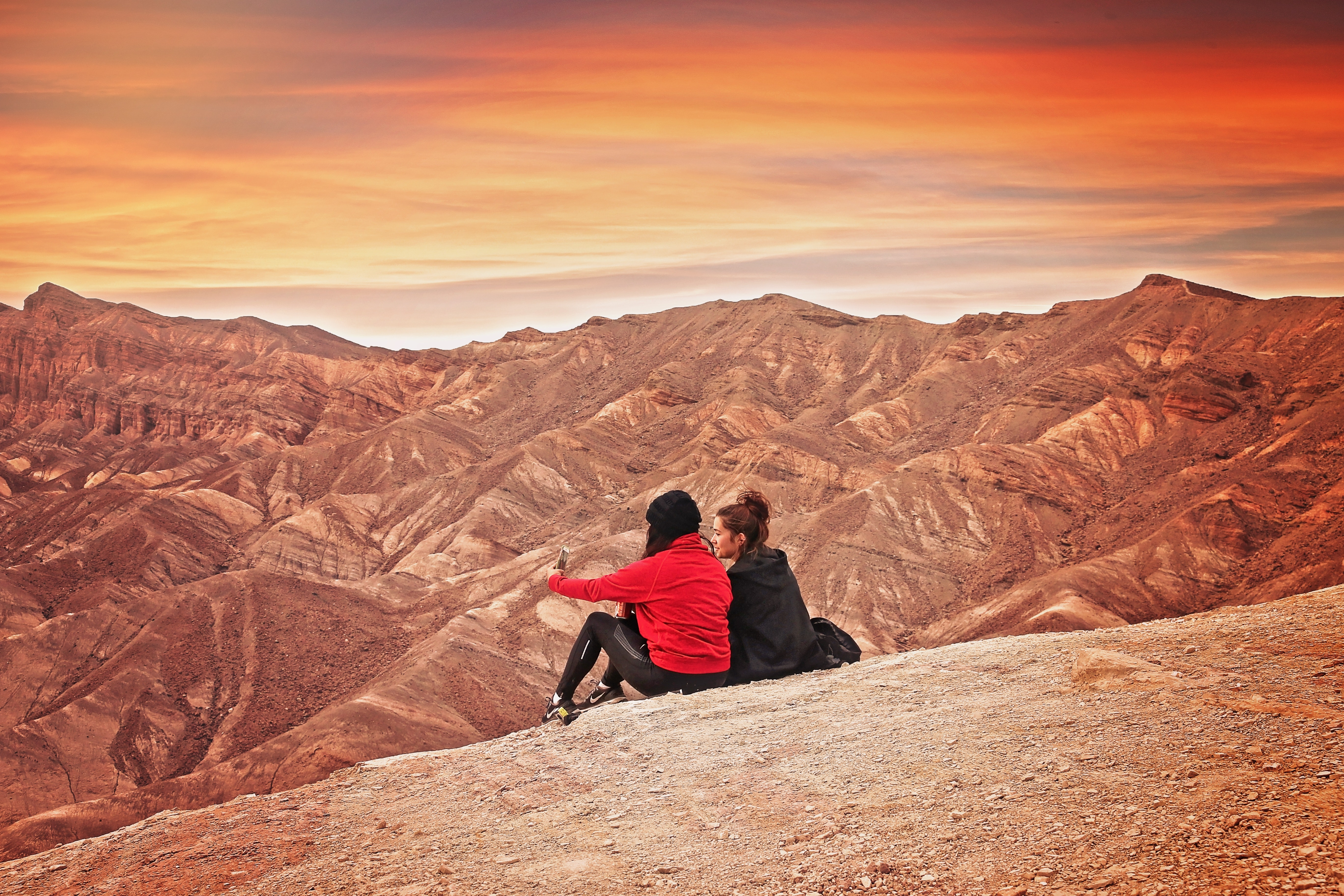 2 woman seating on the mountain cliff during golden hour photo