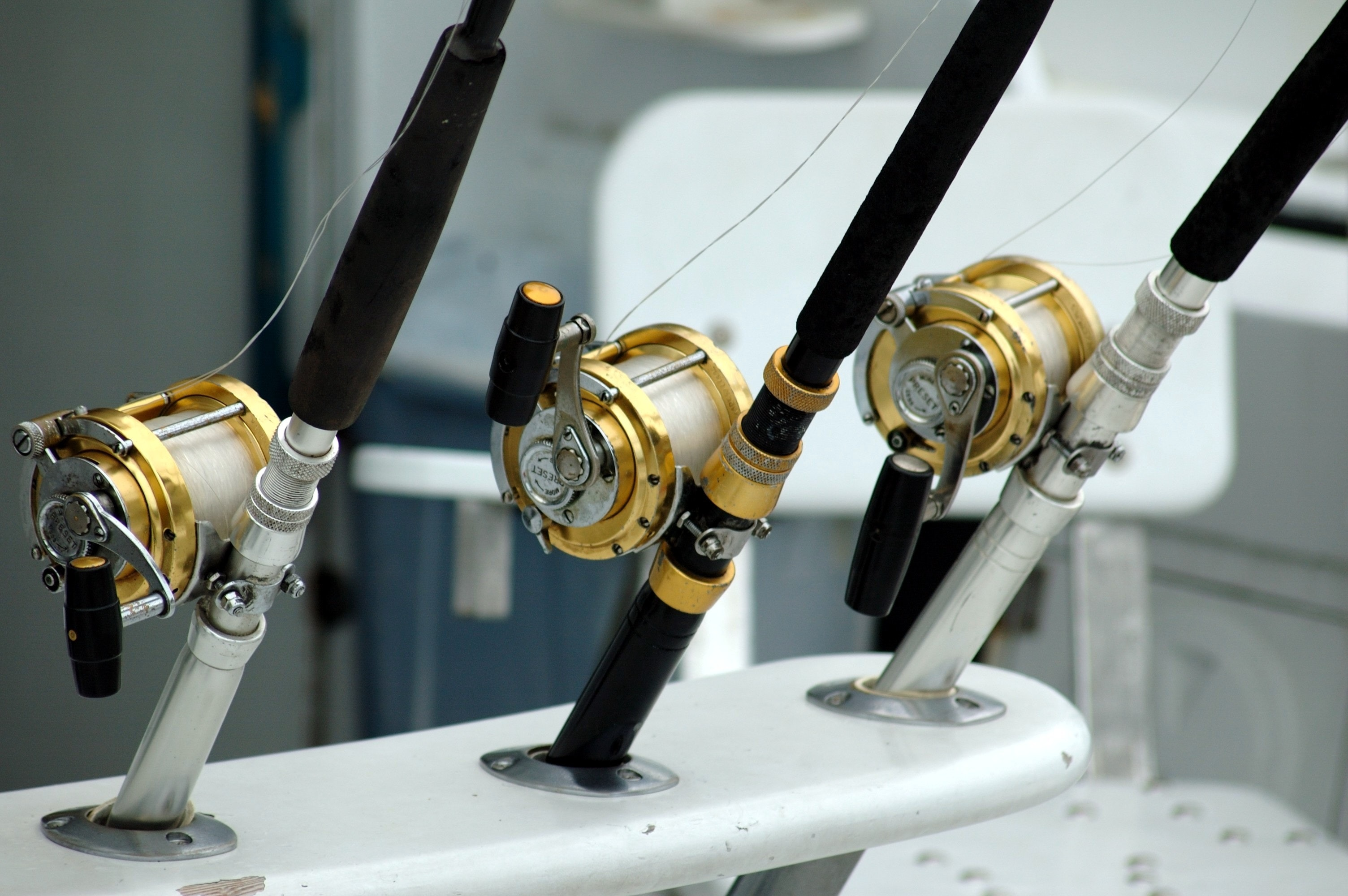 3 lined brass and black fishing reel photo