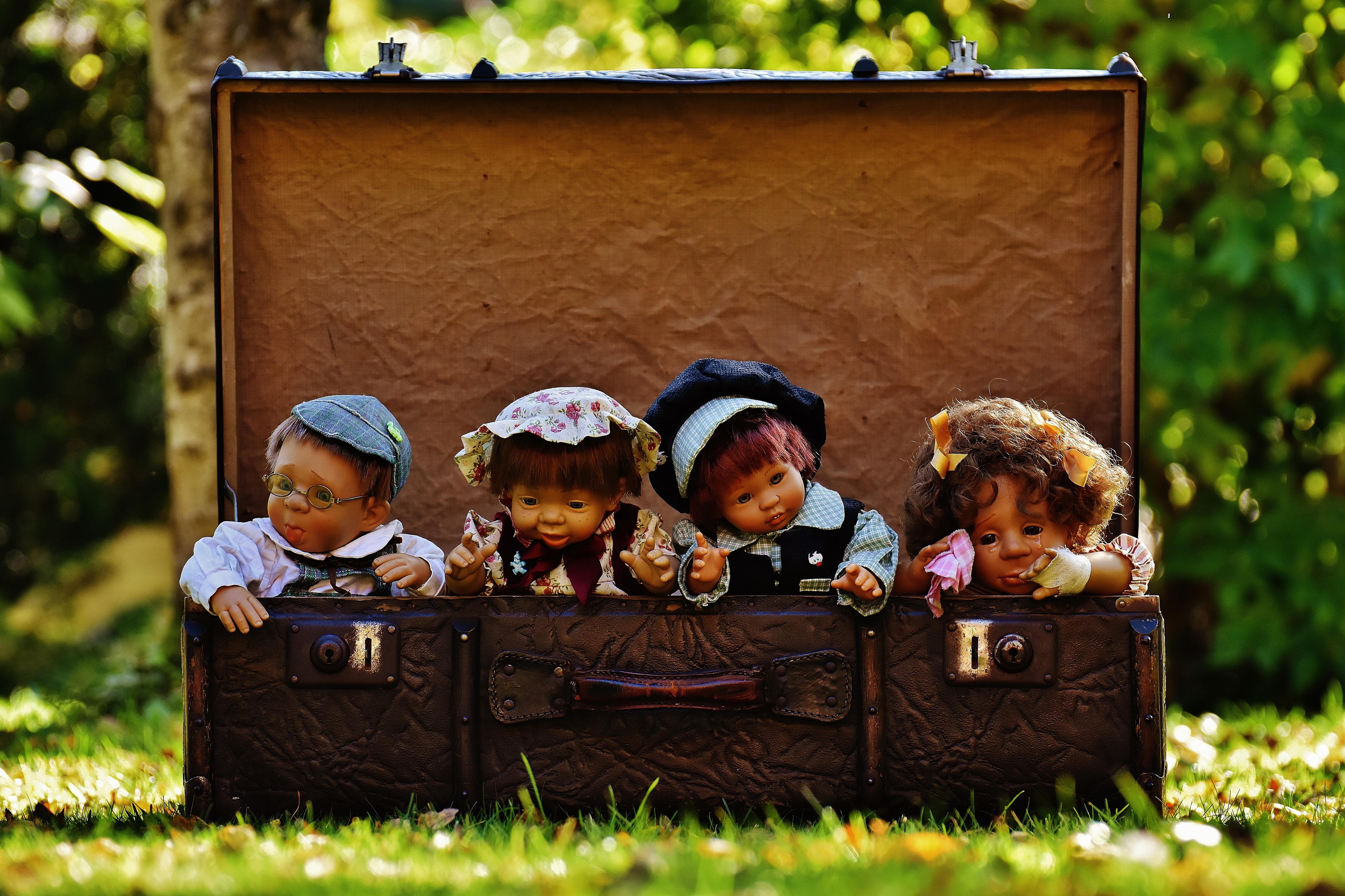 4 porcelain dolls in brown rectangular box photo