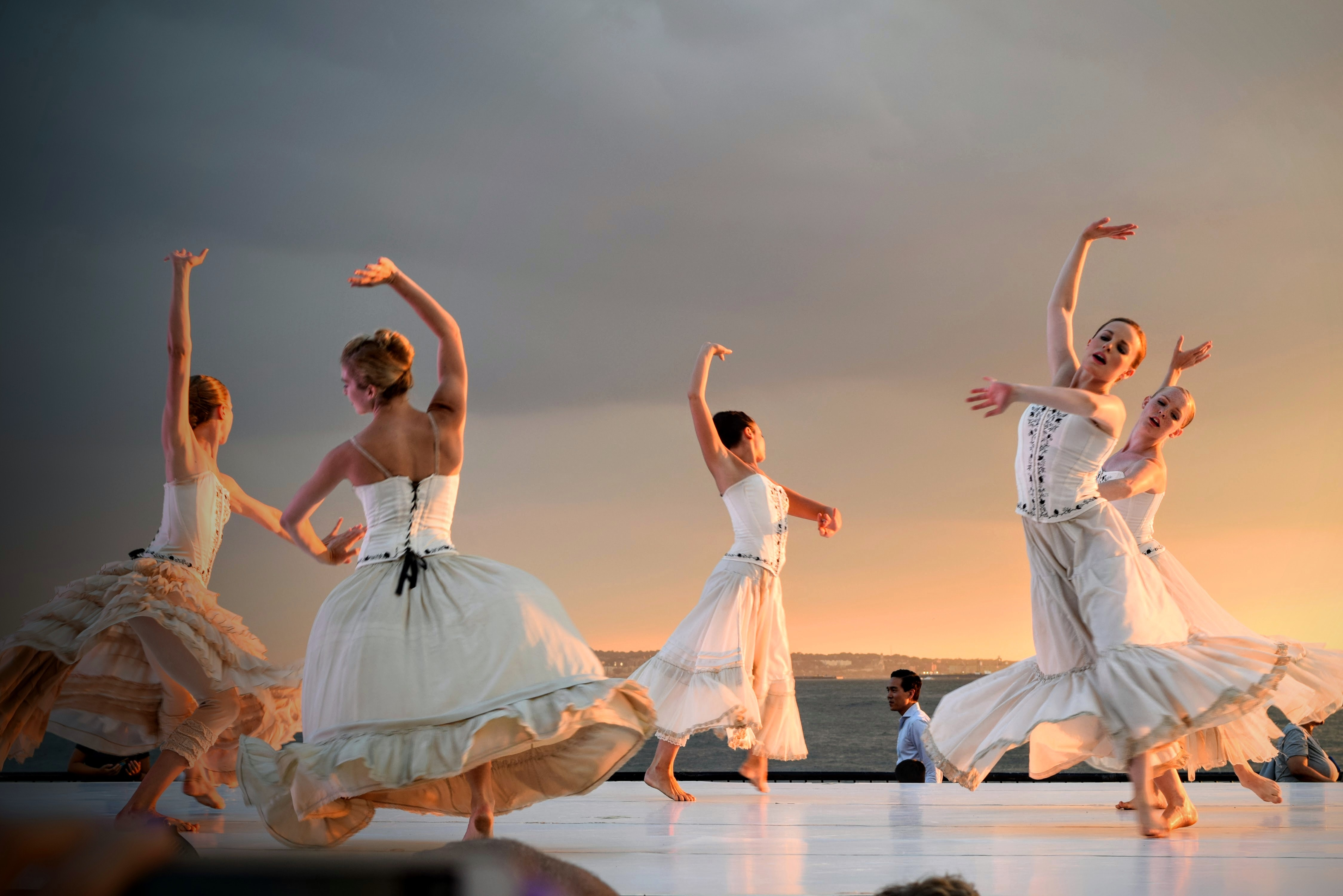 5 women in white dress dancing under gray sky during sunset photo