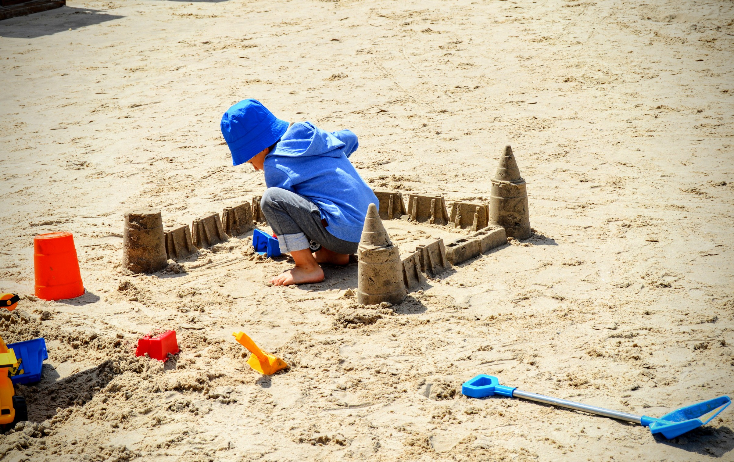 A child plays with sand, sculpting a sand castle on a sandy beach photo