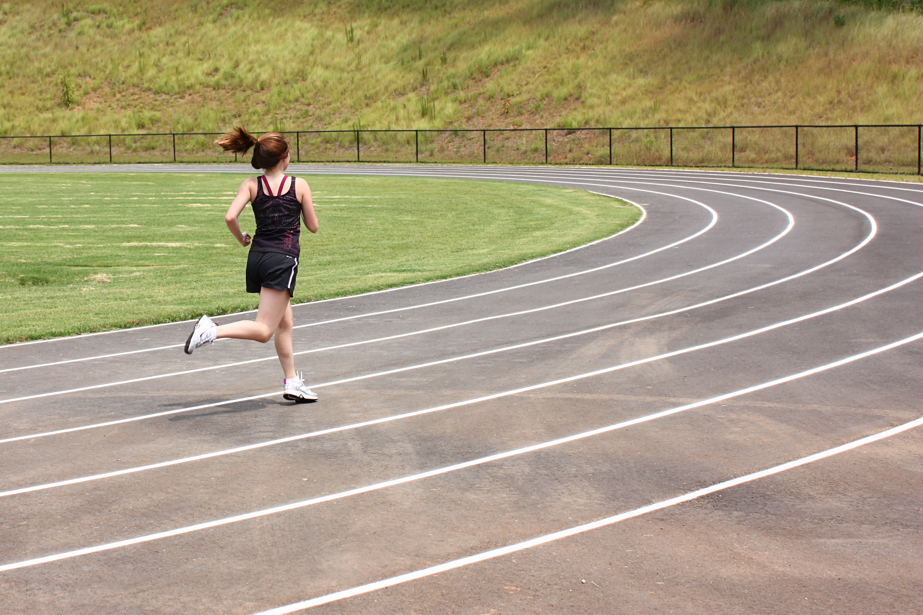 A cute young girl running on a track photo