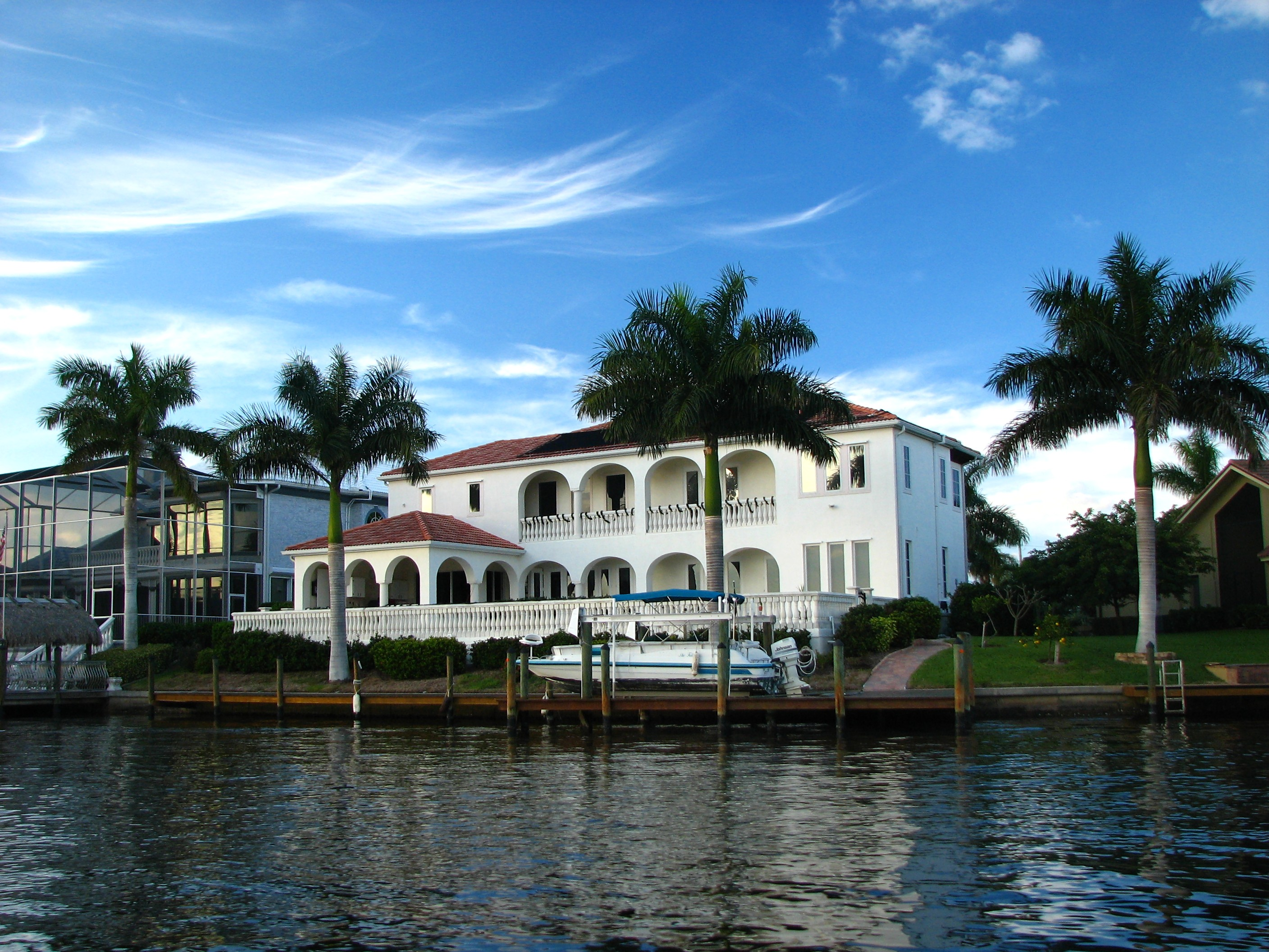 A fancy house along the water with palms photo