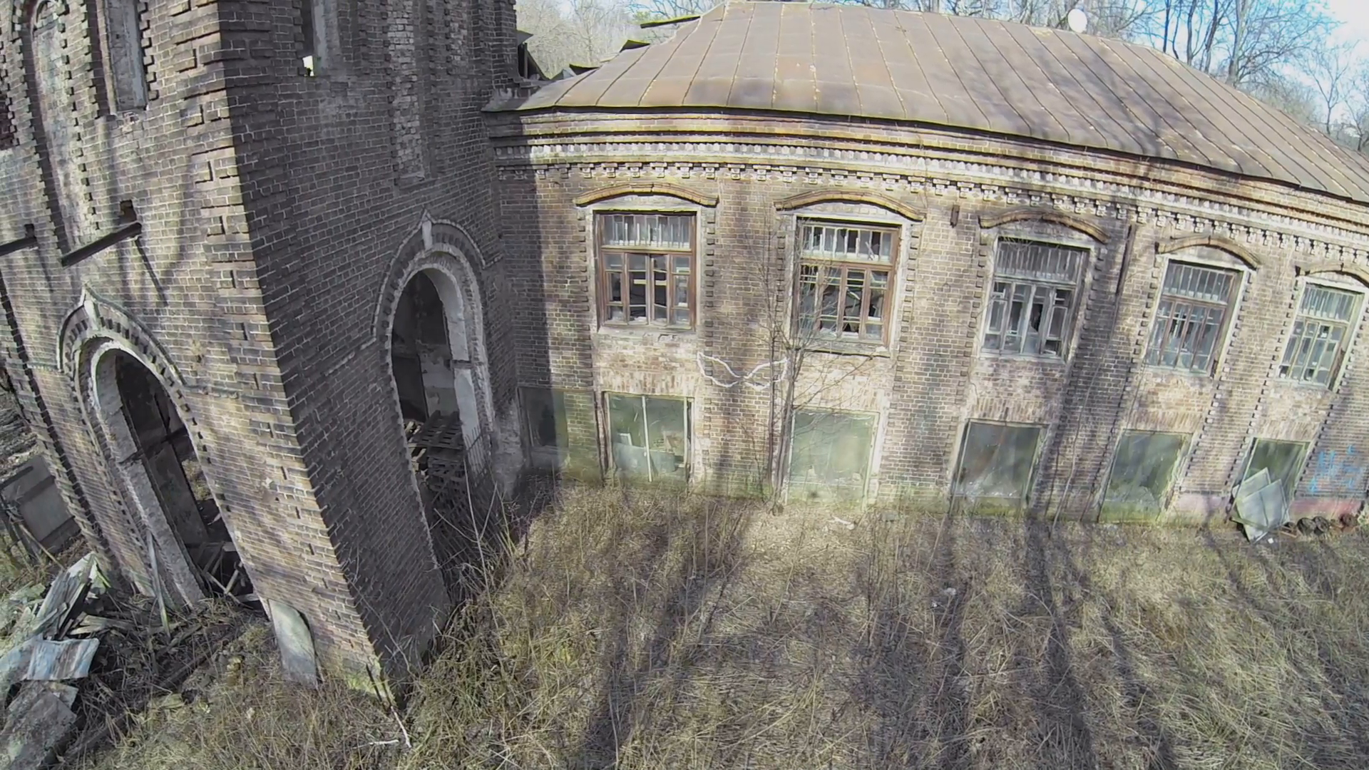 Abandoned building with entrance in tower lit by sunlight. Aerial ...