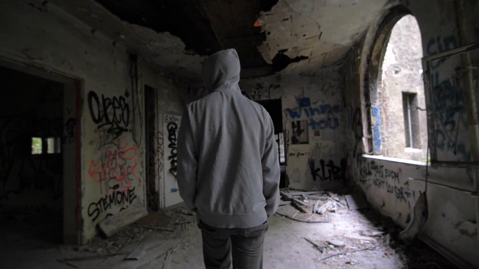 Slow motion of a guy with hood walking through abandoned building ...