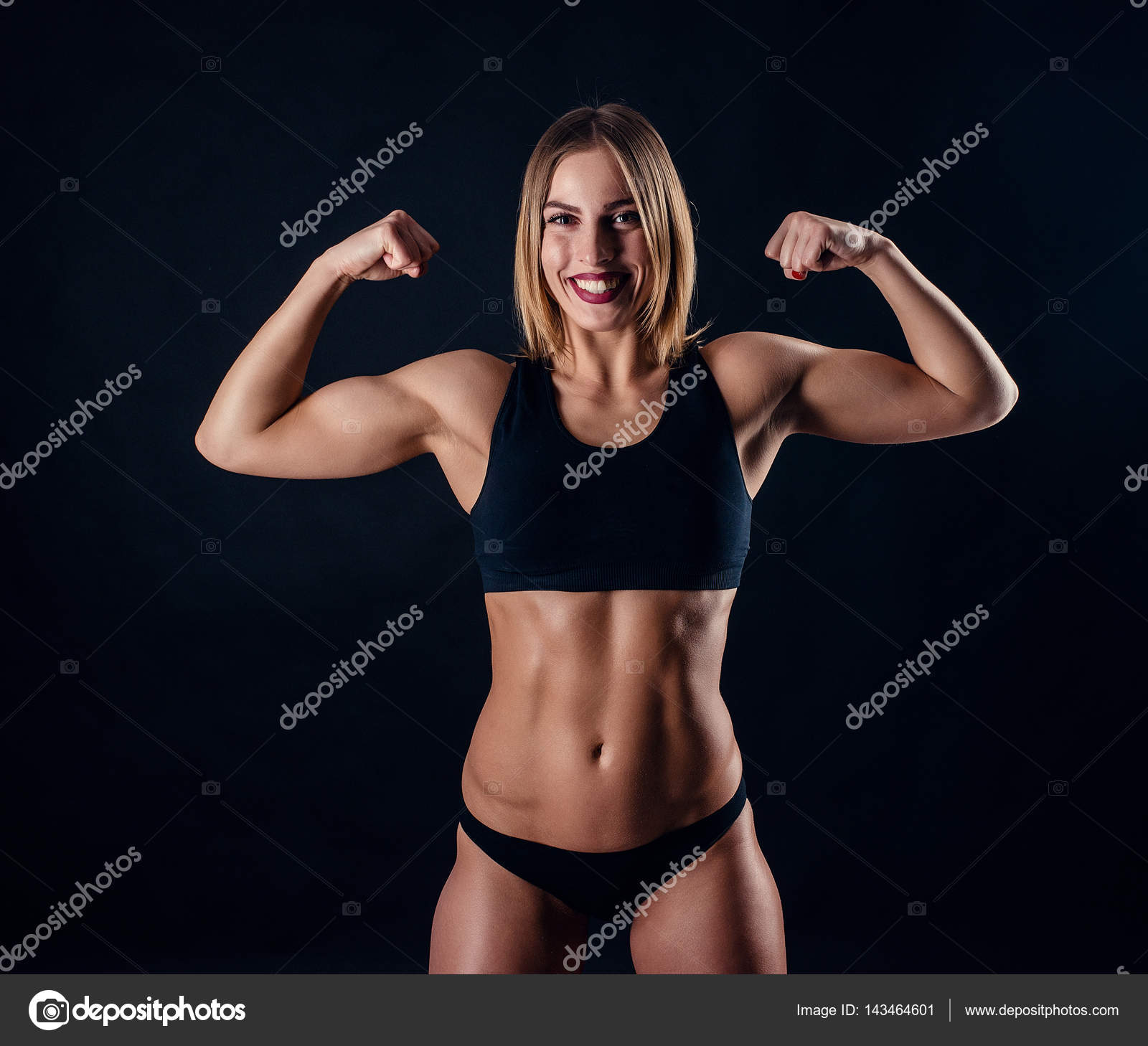 Sporty girl with great muscles in black sportswear. Tanned young ...