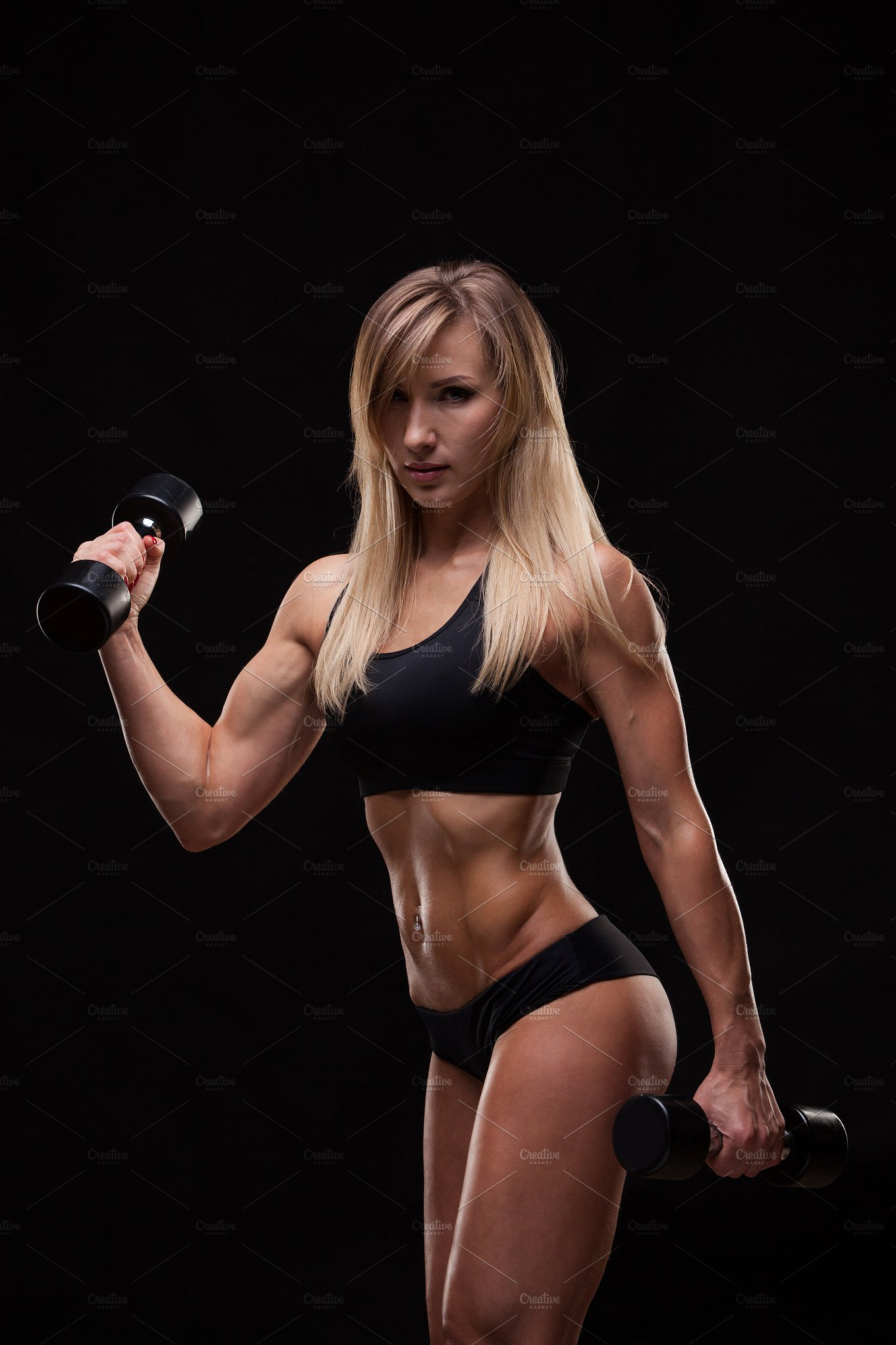 Beautiful athletic woman pumping muscles with dumbbells, isolated on ...
