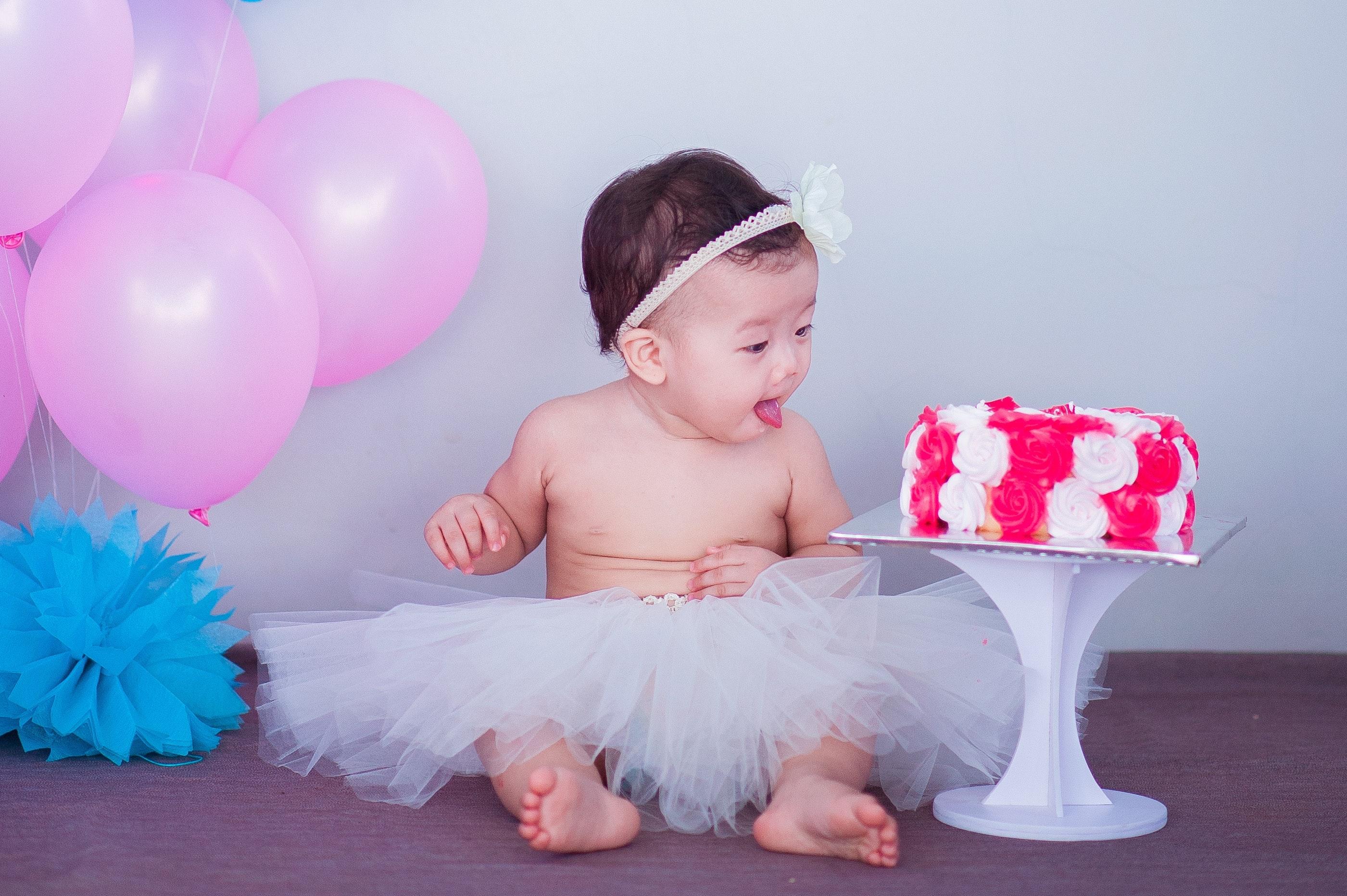 Baby in white tutu skirt beside cake photo