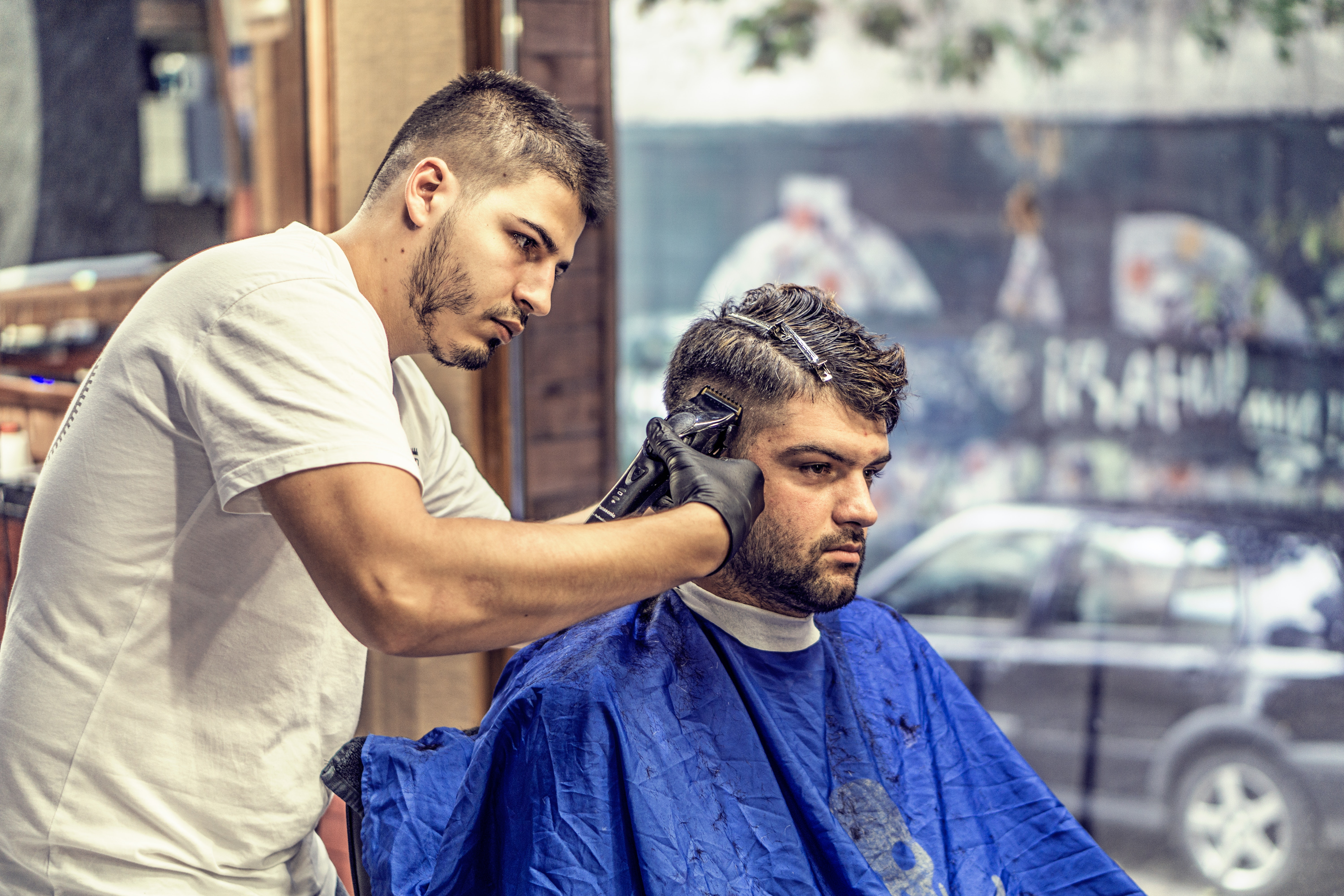 Barber in White Shirt Trimming Man's Hair in Blue Textile While Sitting Nearby Glass Window, People, Stylish, Men, Hairdresser, HQ Photo