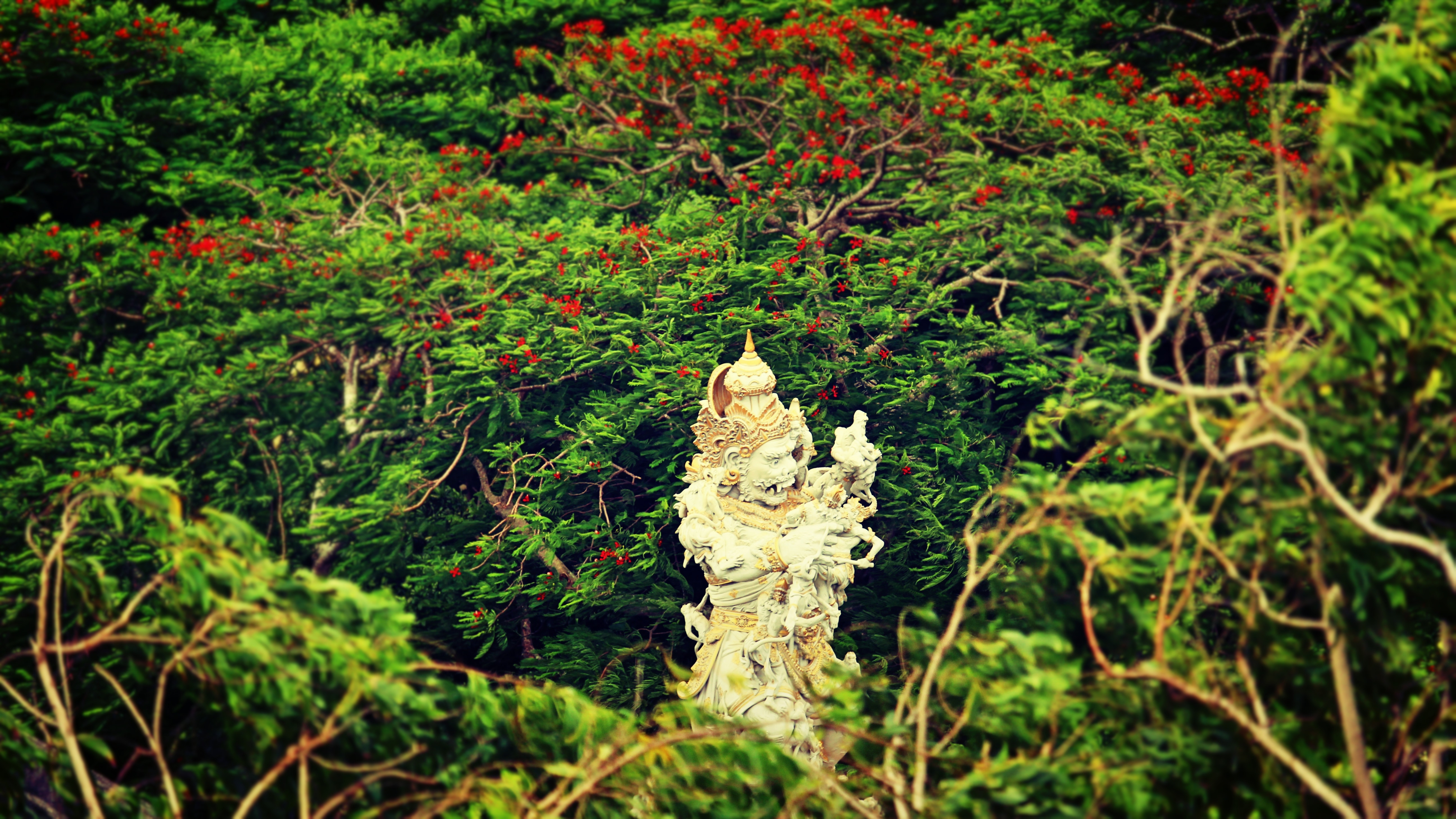 Beige hindu statue surrounded by trees at daytime photo