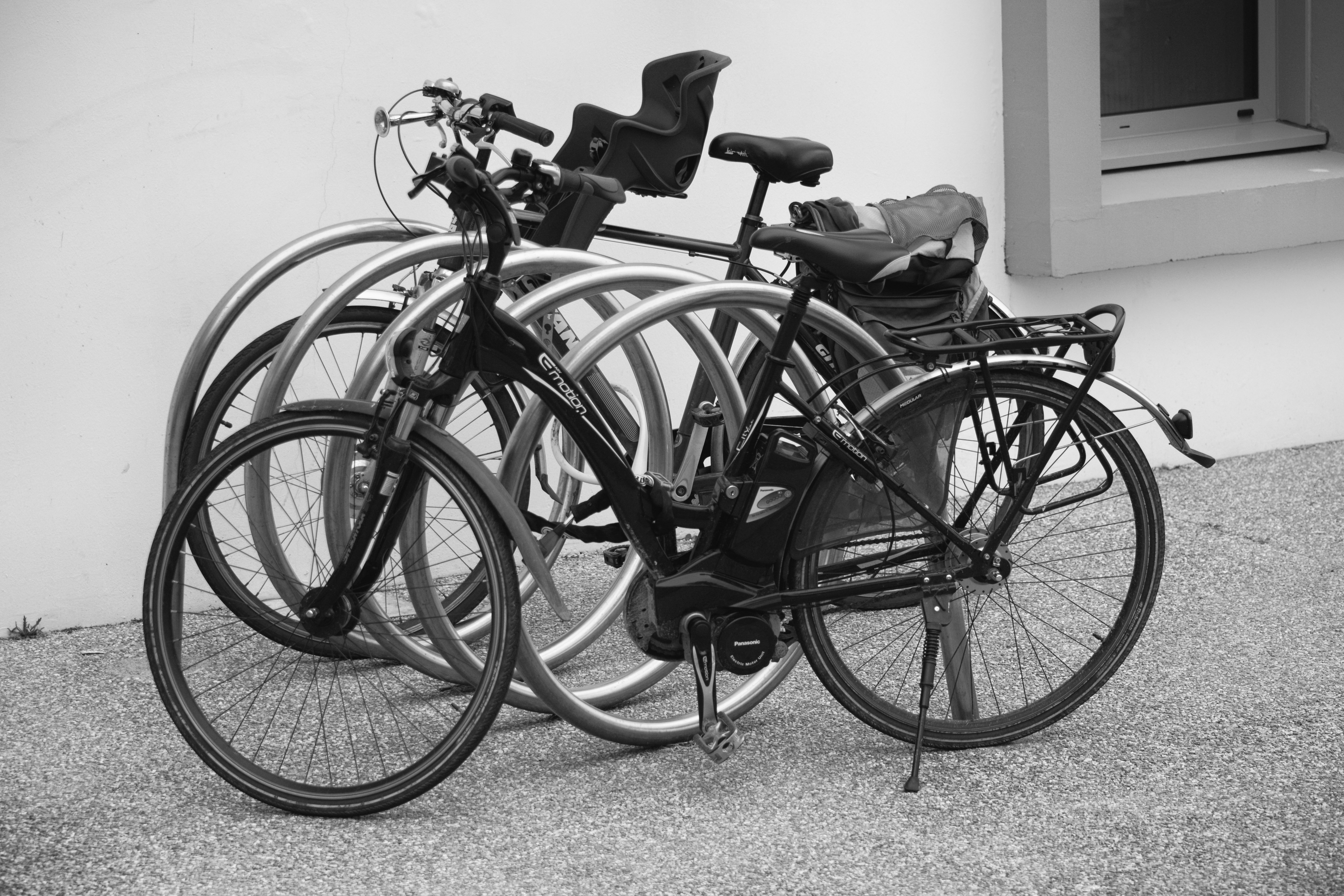 Black and grey bicycle park beside wall photo