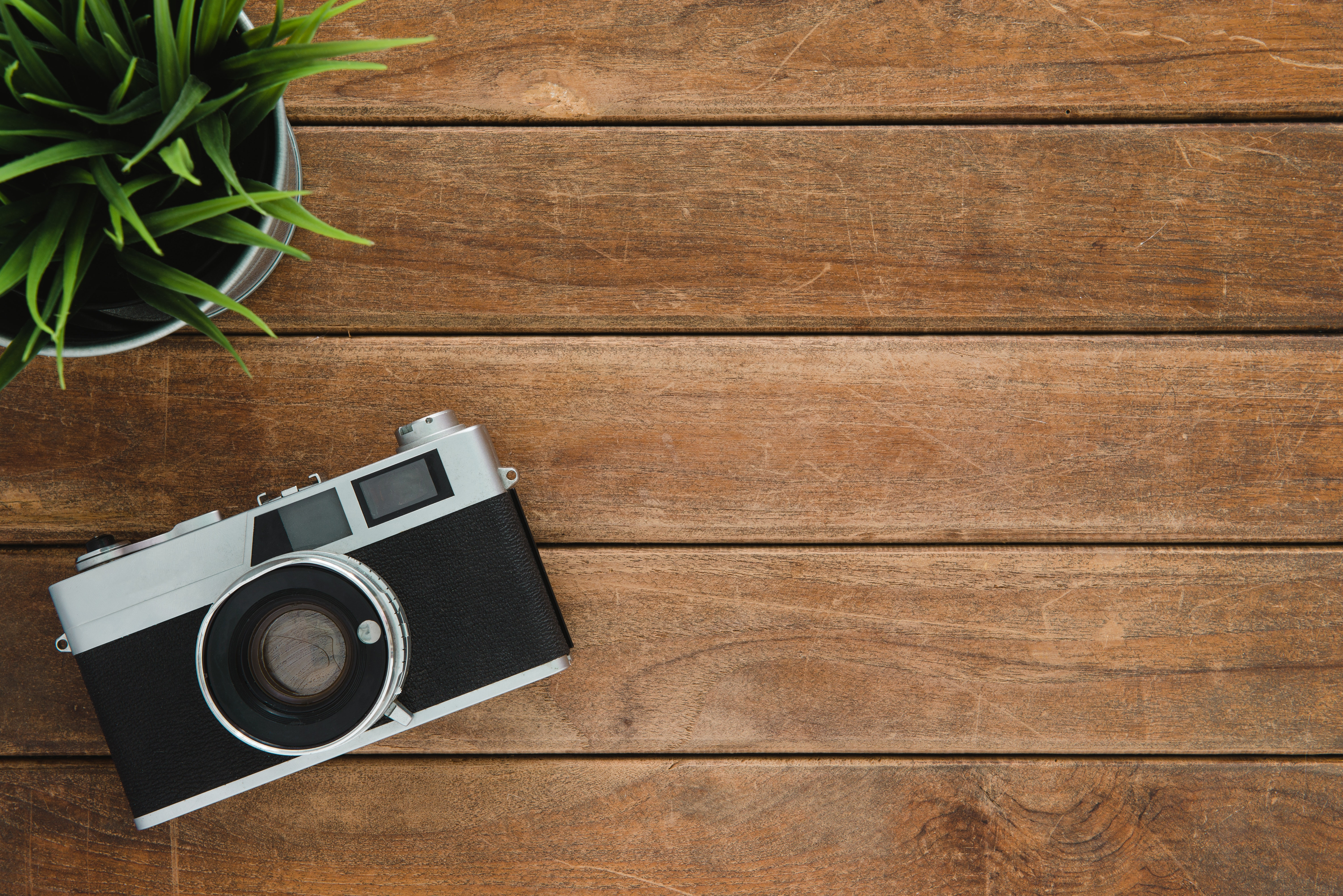 Black and silver film camera on brown wooden surface photo