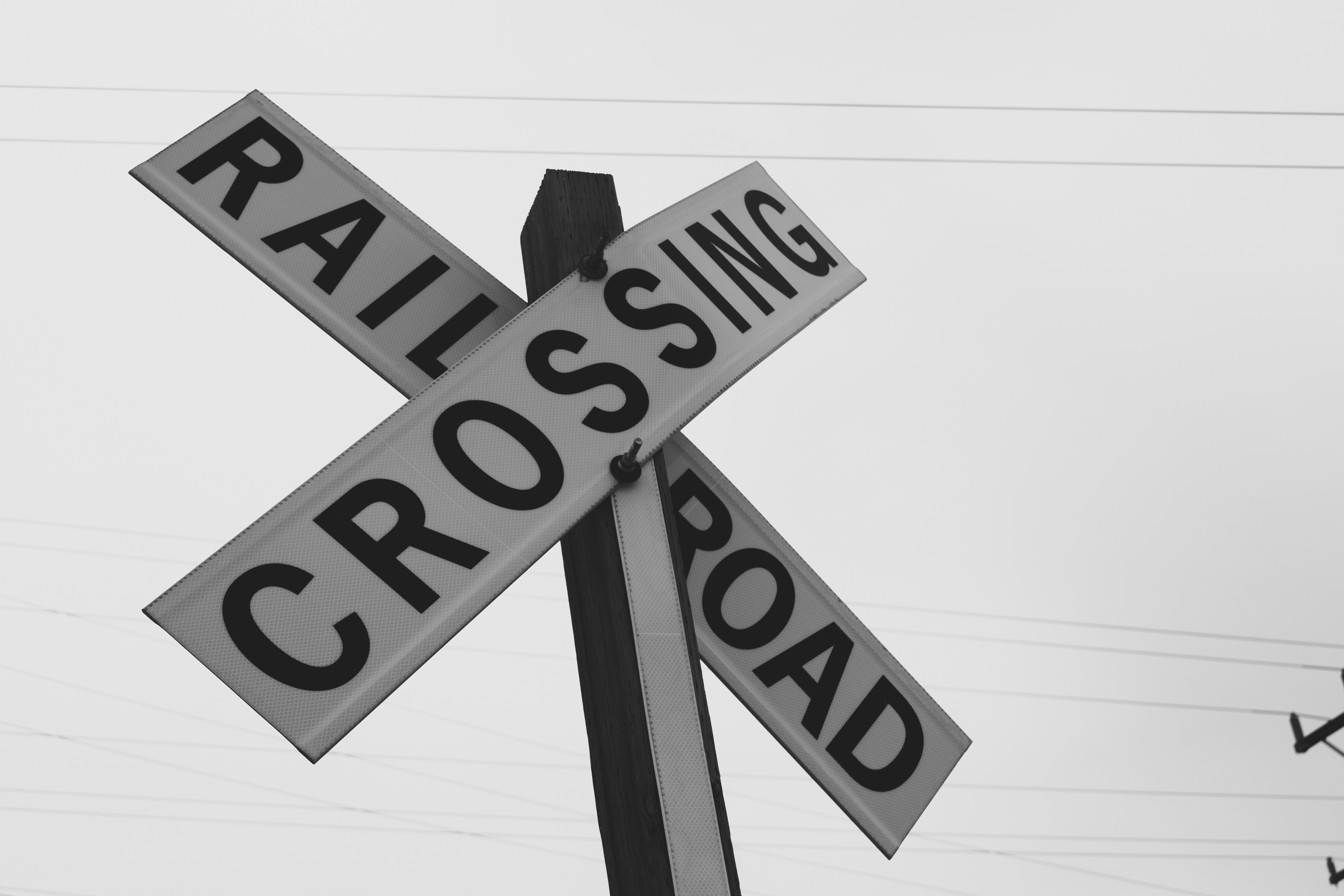 Black and white photo of a road sign near the railway