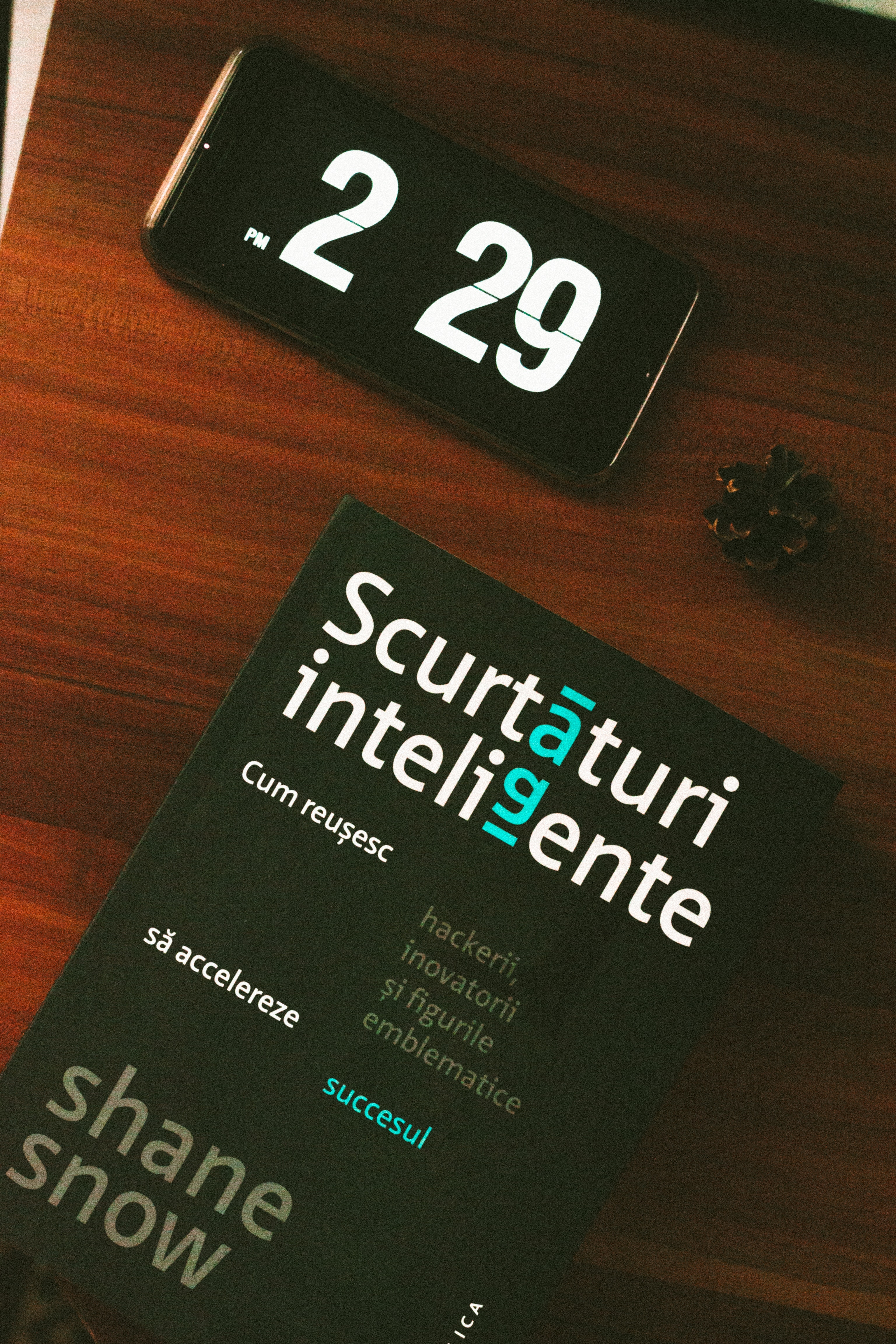 Black android smartphone beside scurtaturi inteligente book photo