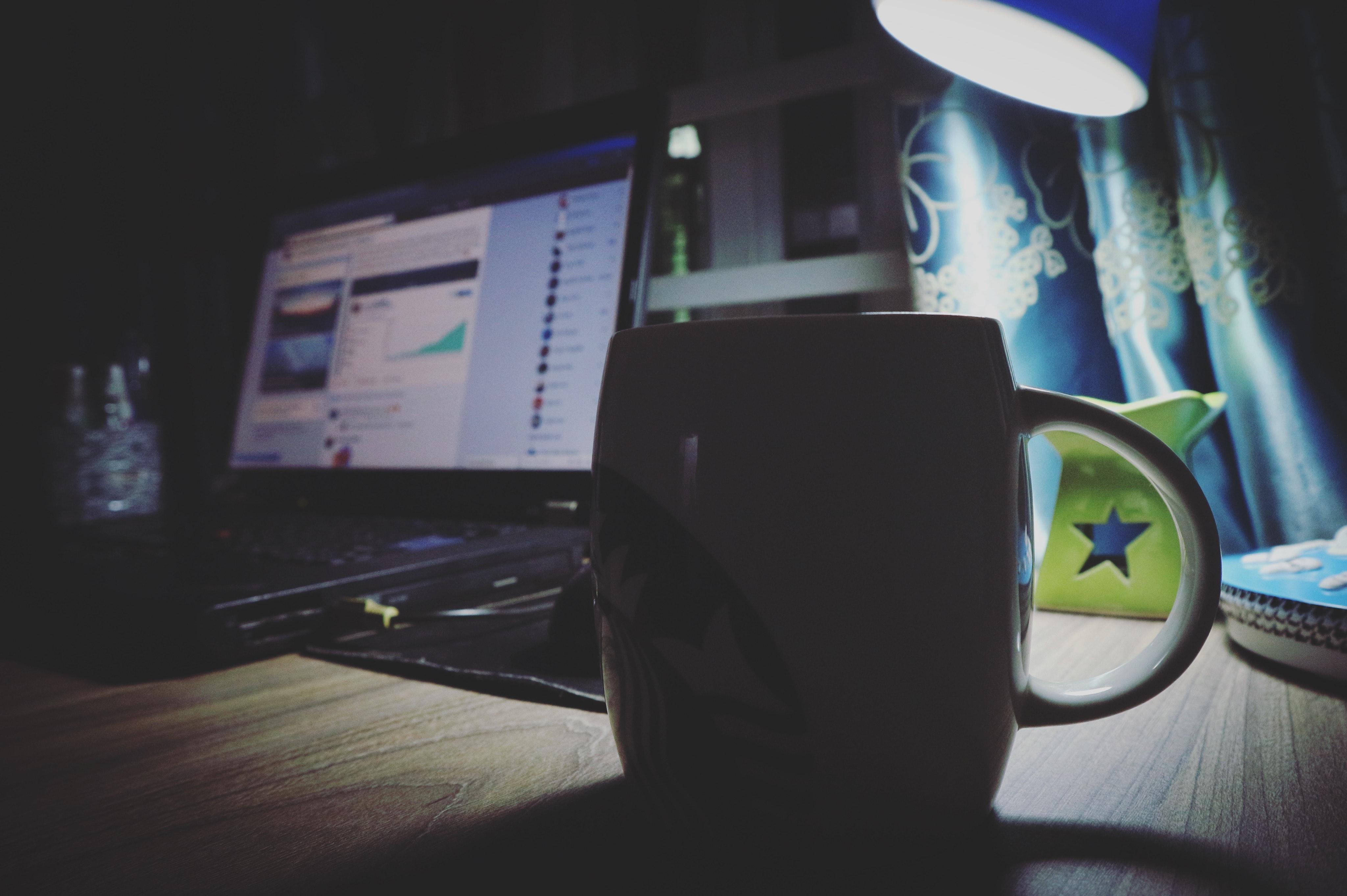 Black ceramic mug near black laptop photo