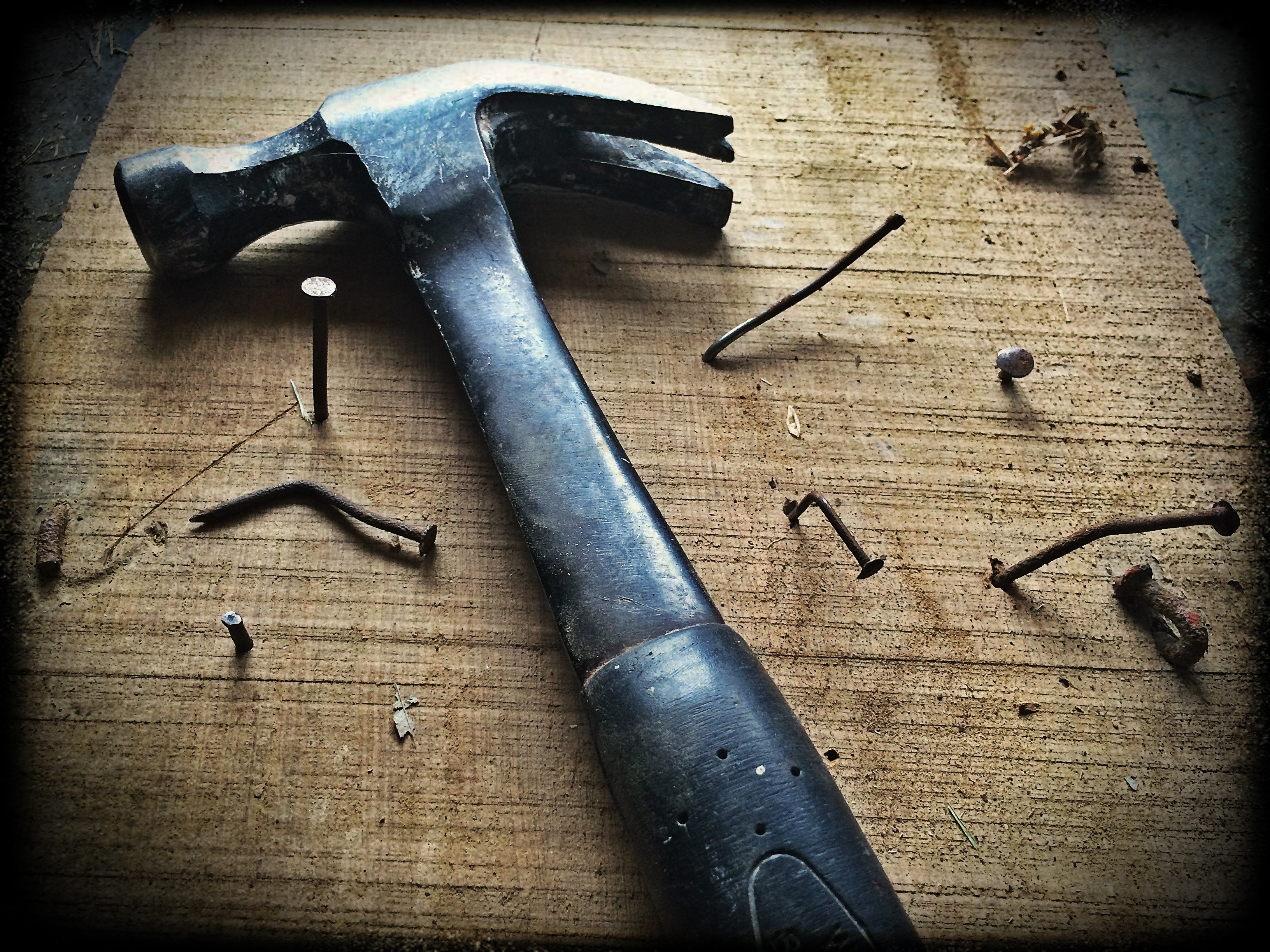 Black claw hammer on brown wooden plank photo
