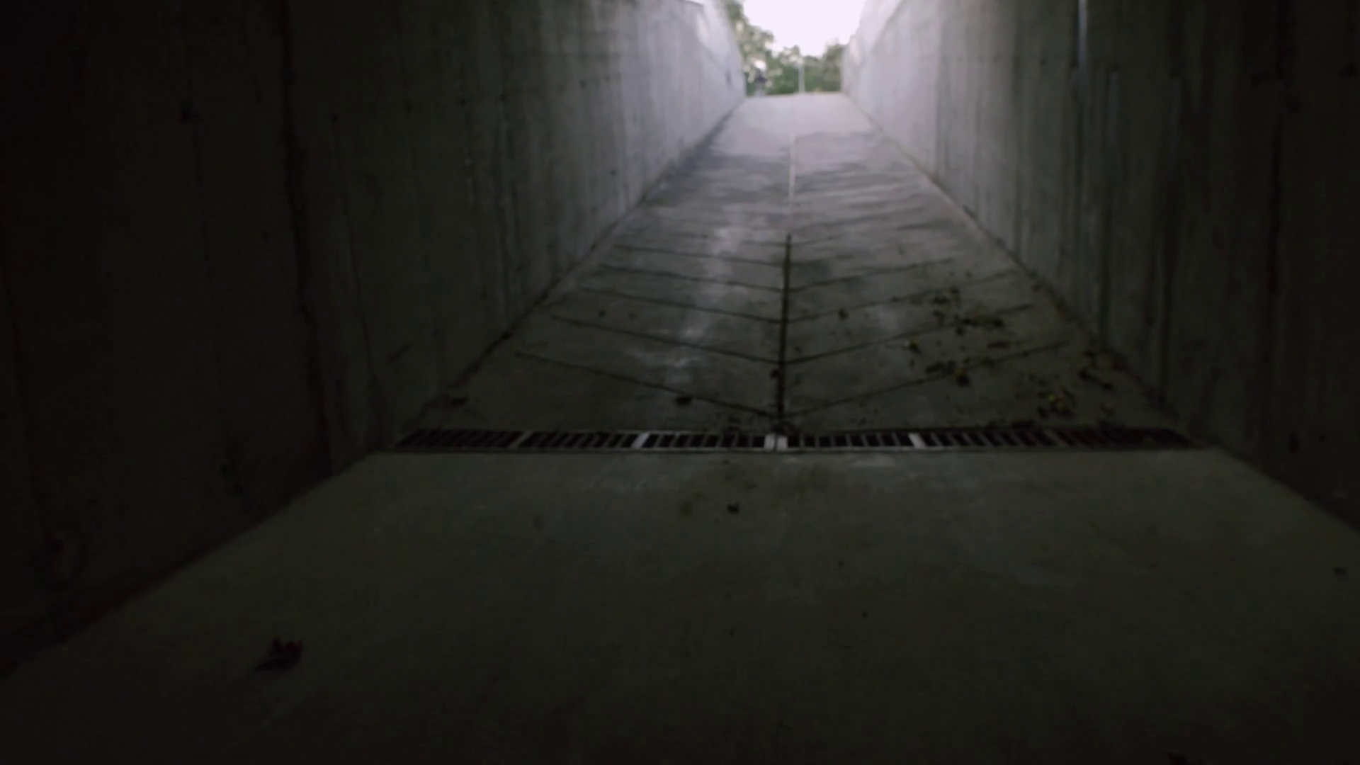 A young girl runs through a dark concrete tunnel to the glowing end ...