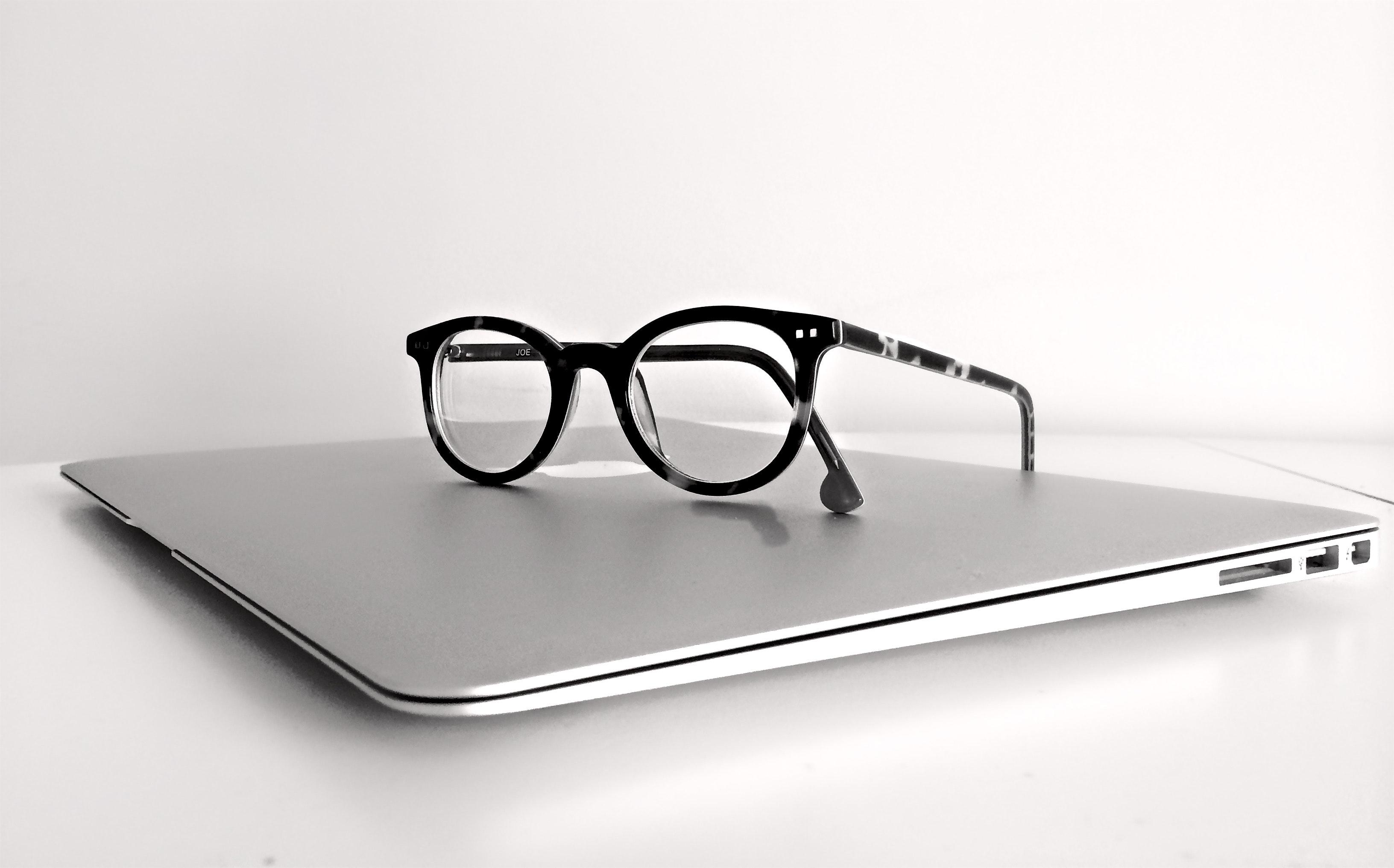 Black frame eyeglasses on silver macbook air photo