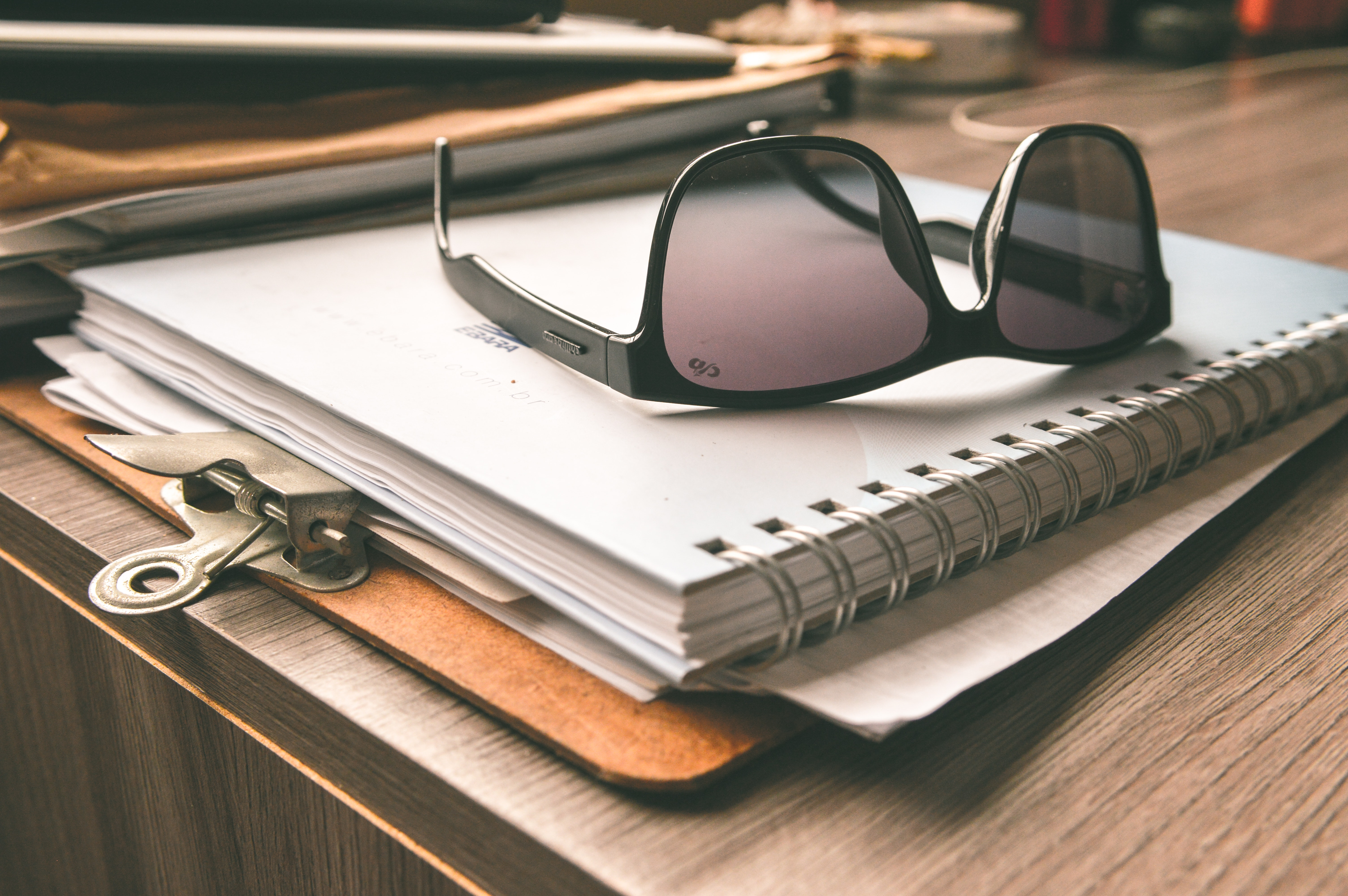 Black frame wayfarer sunglasses on white notebook photo