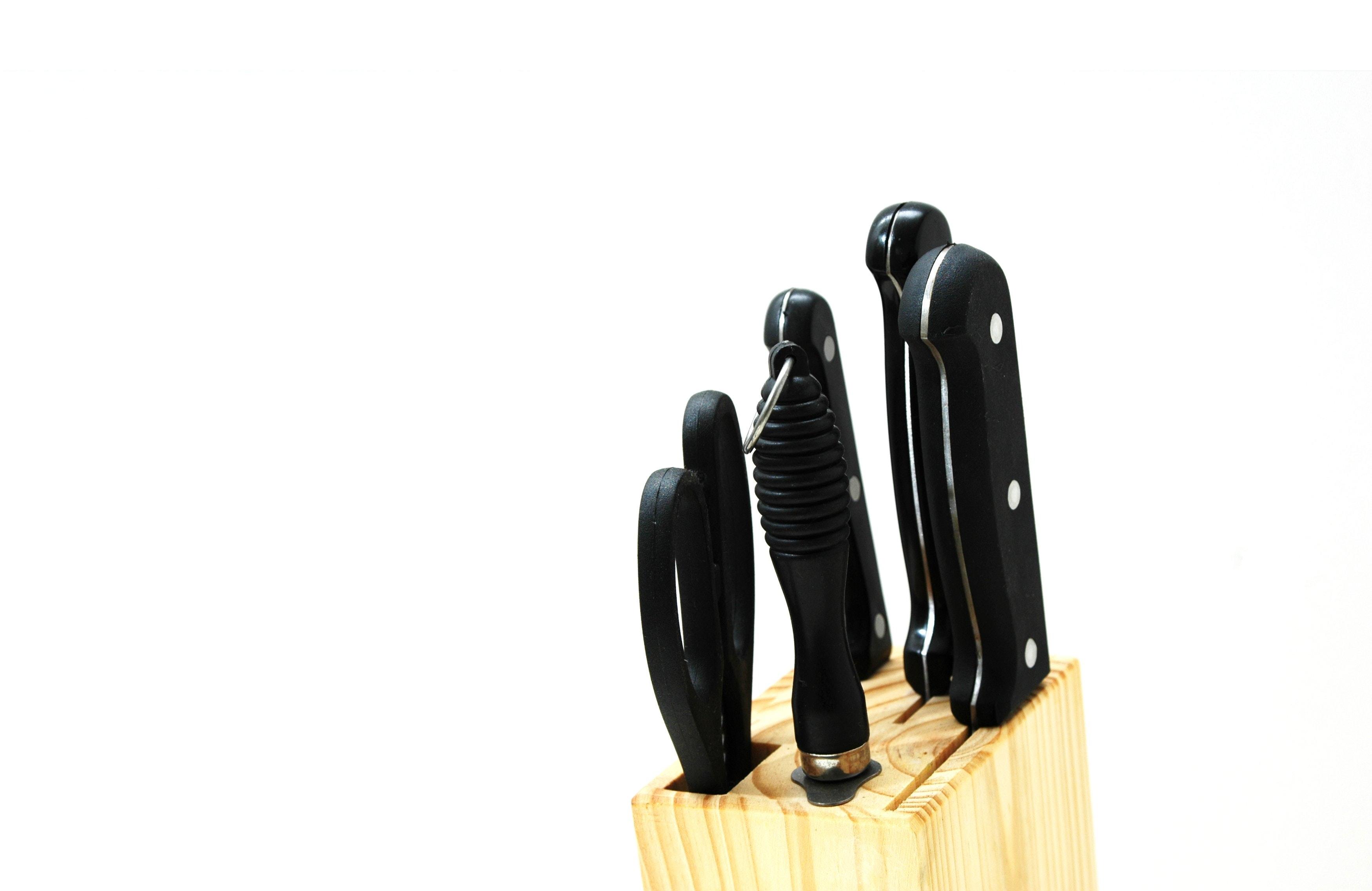 Black handled kitchen knife on beige wooden pallet photo