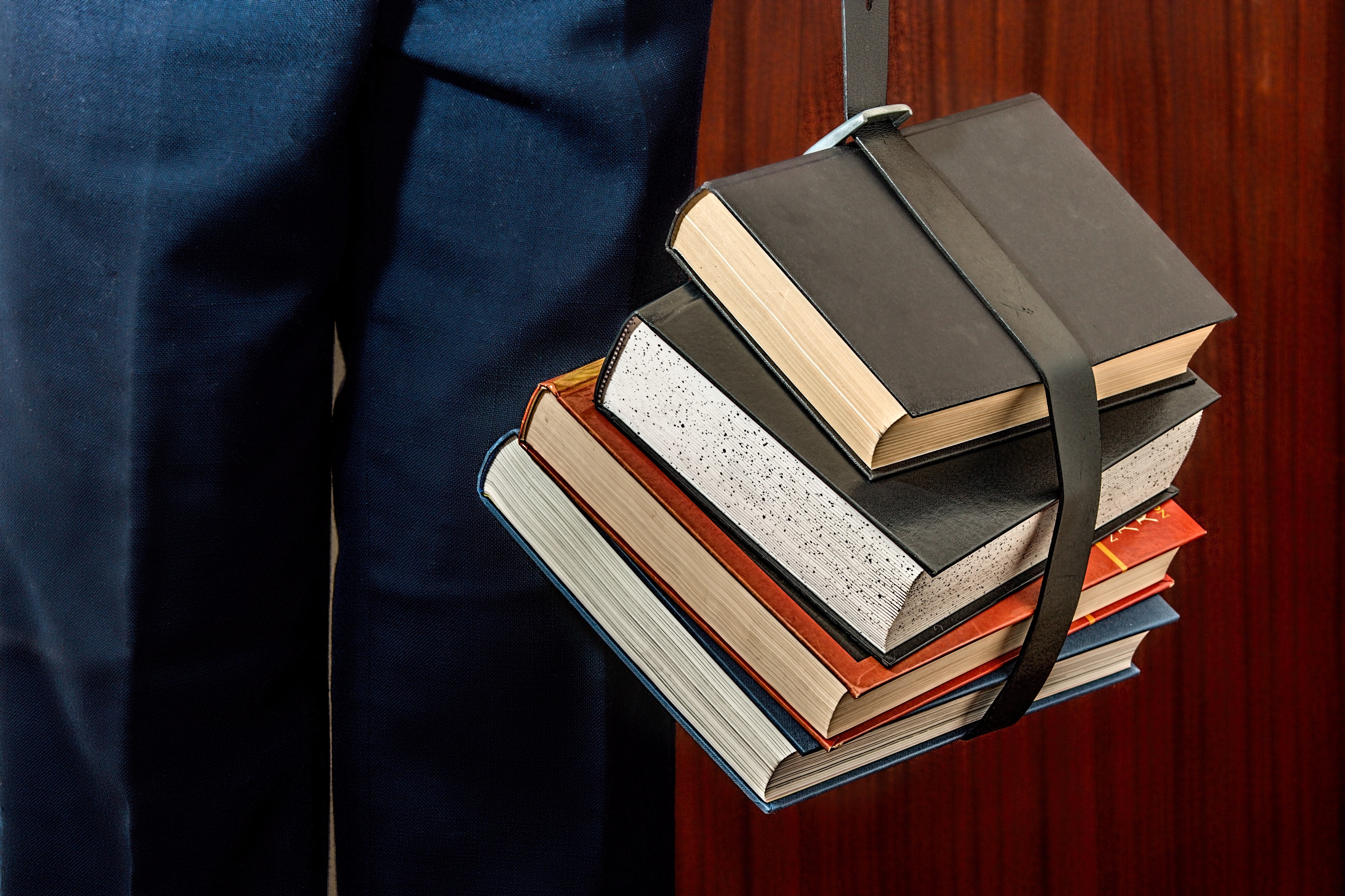 Black leather book strapped around four books photo