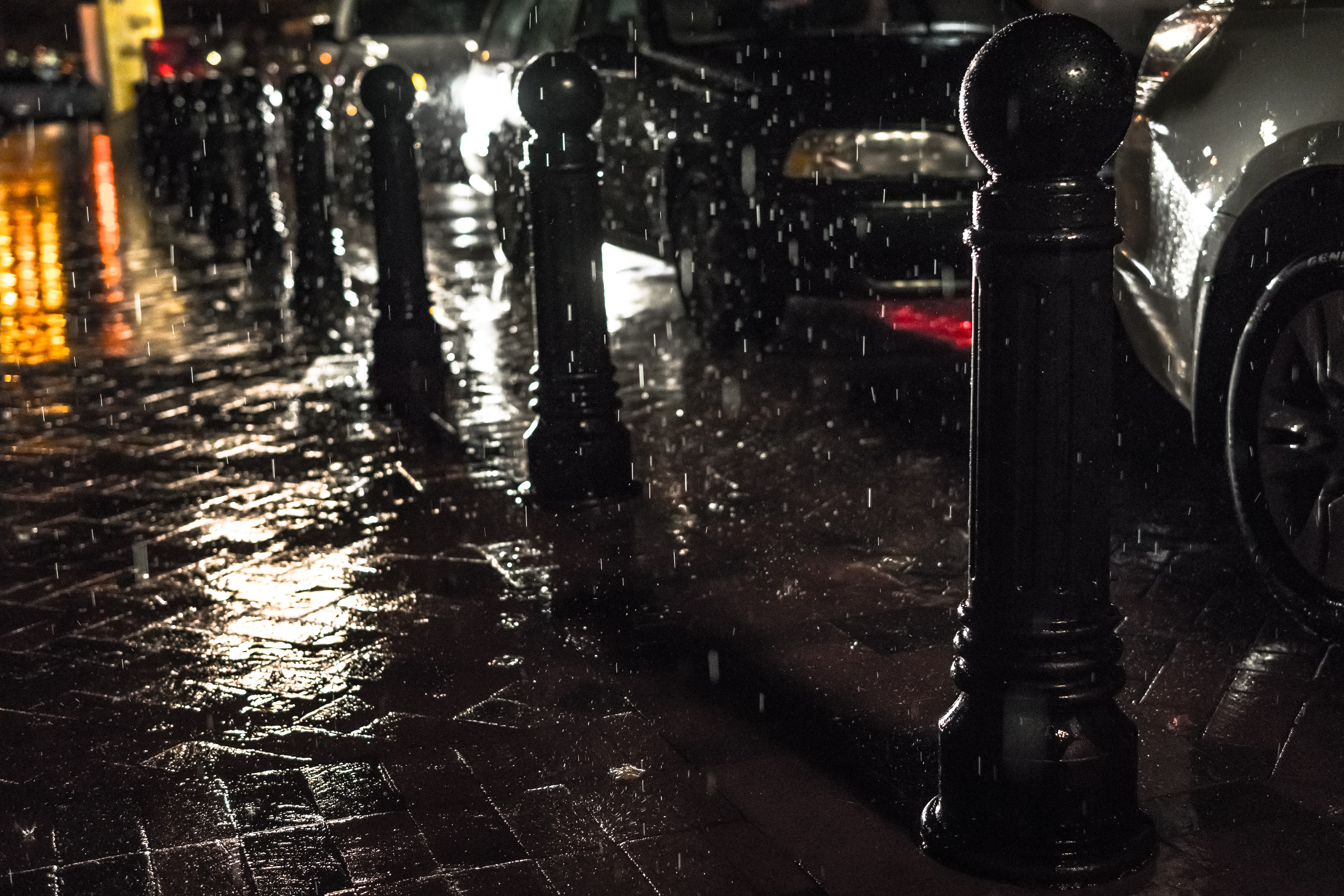 free photo black posts on black pavement beneath falling rain