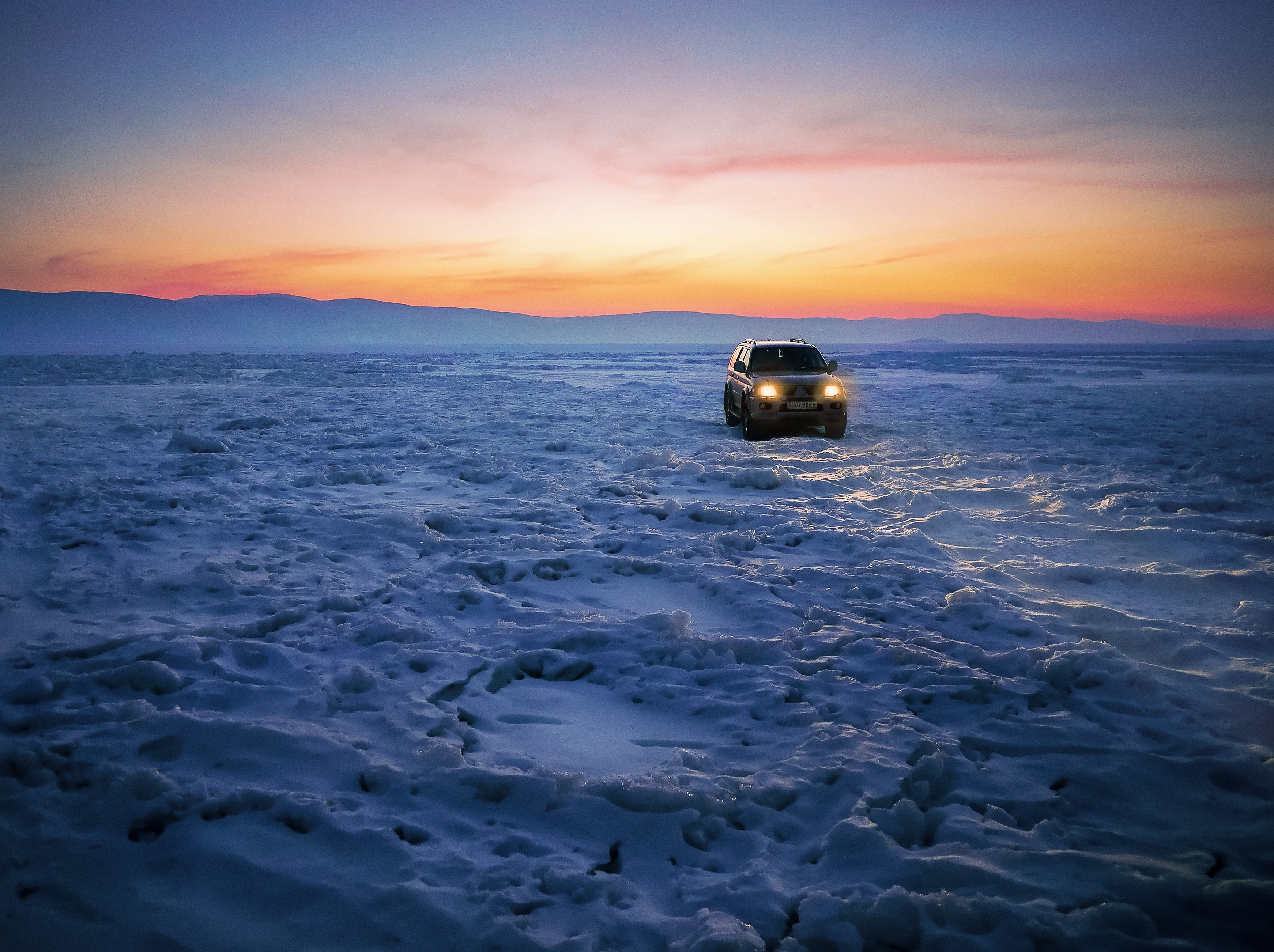 Black suv on snow during golden hour photo