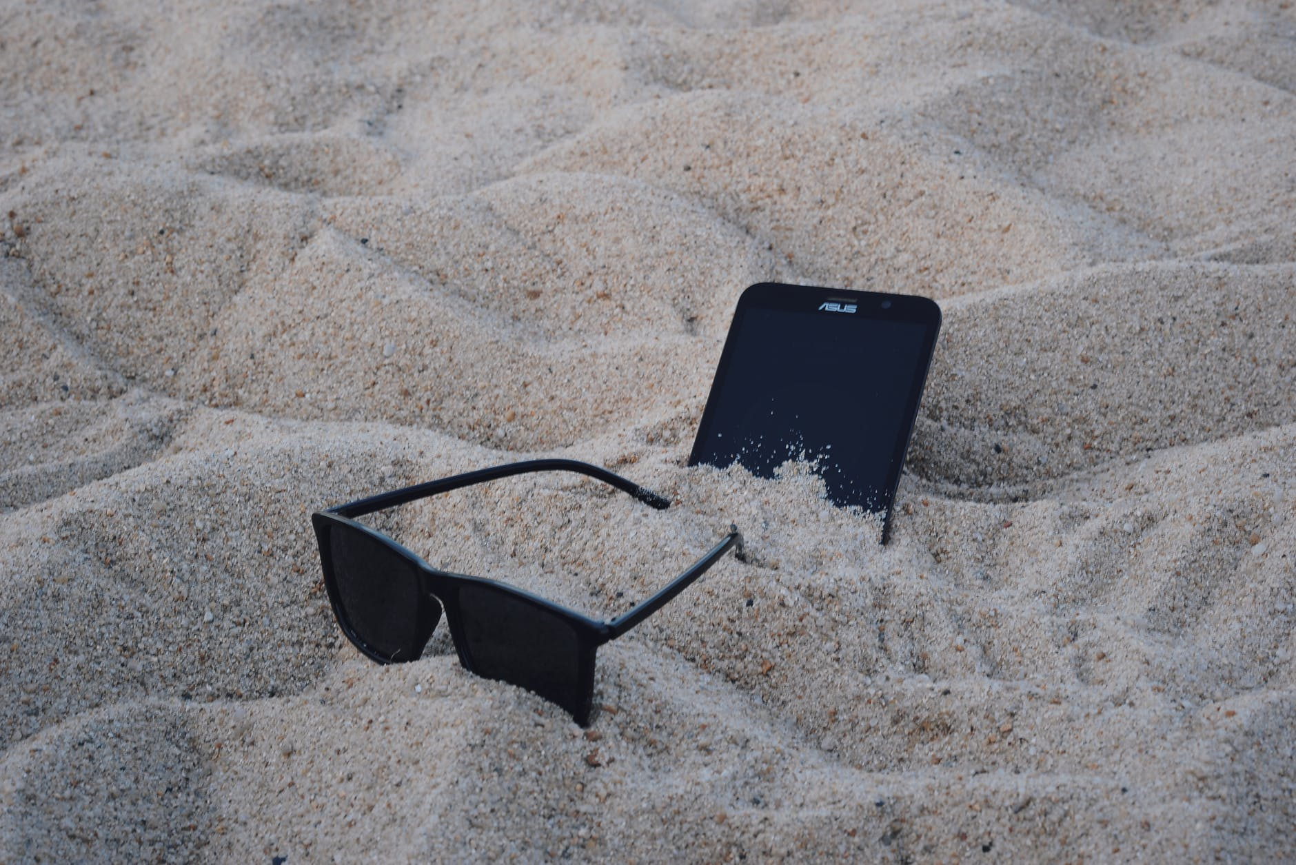 Black wayfarer-style sunglasses beside black asus android smartphone on brown sand photo