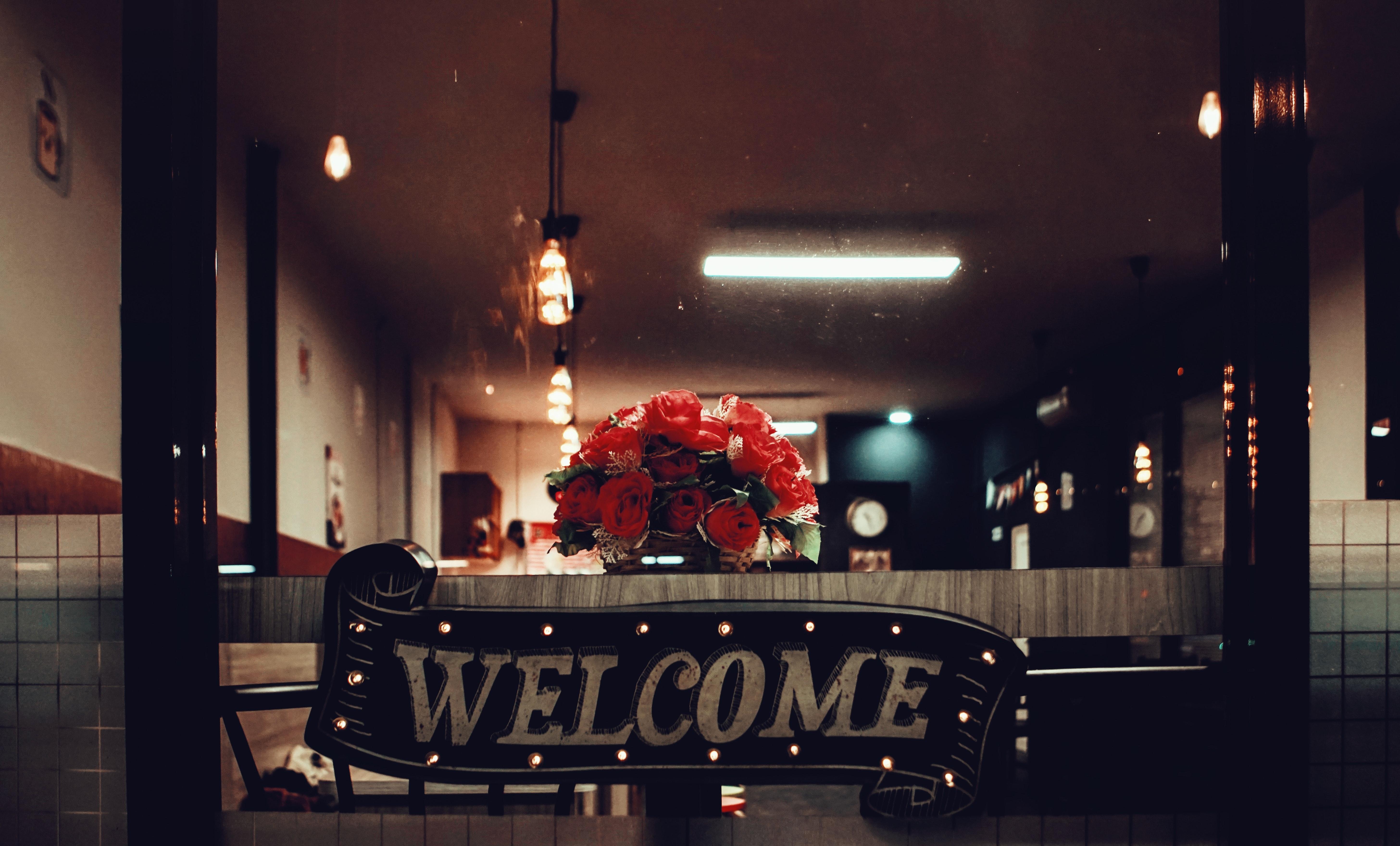 free photo black welcome signage under pendant lamp photography