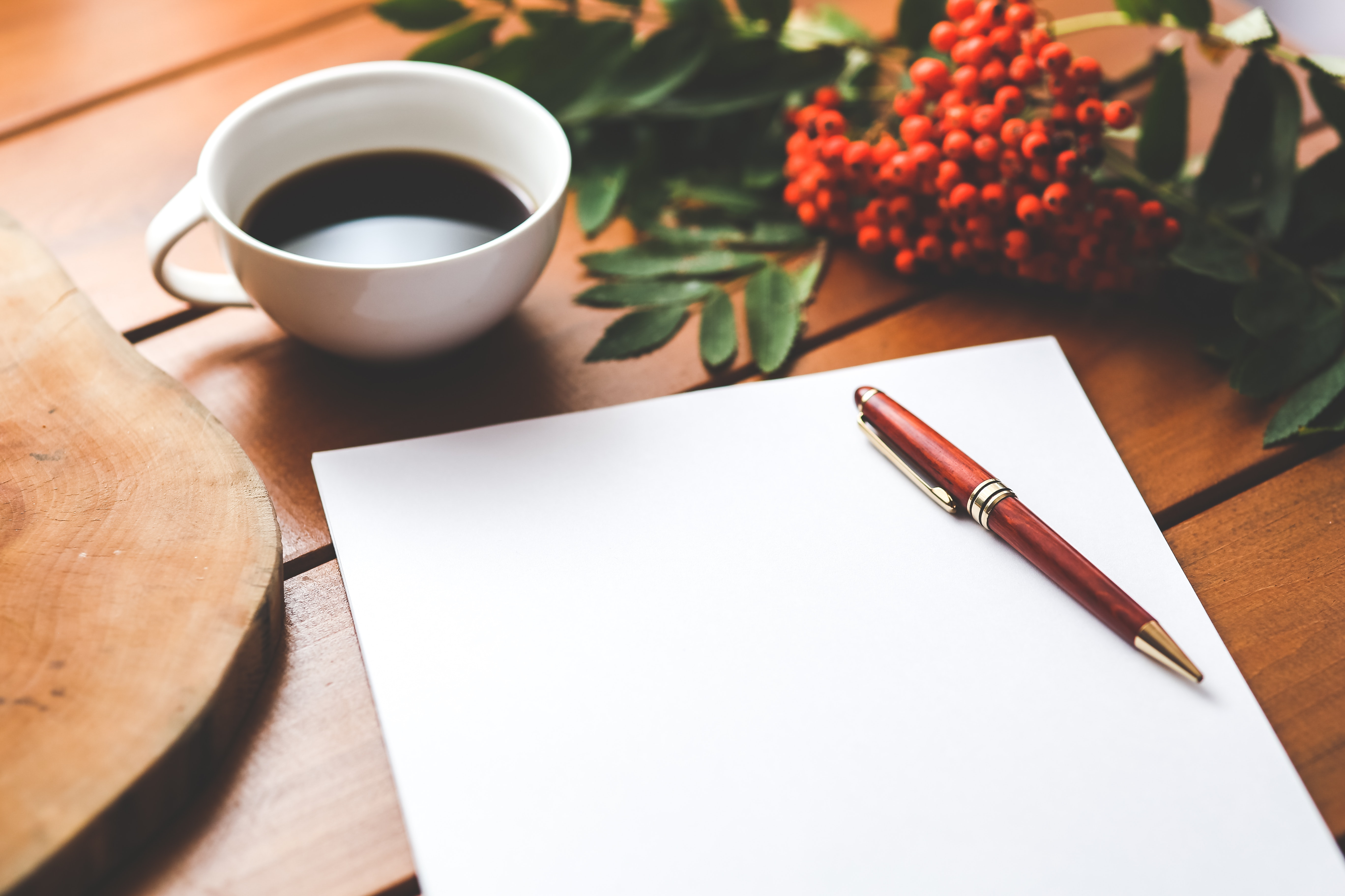 Blank paper with pen and coffee cup on wood table photo