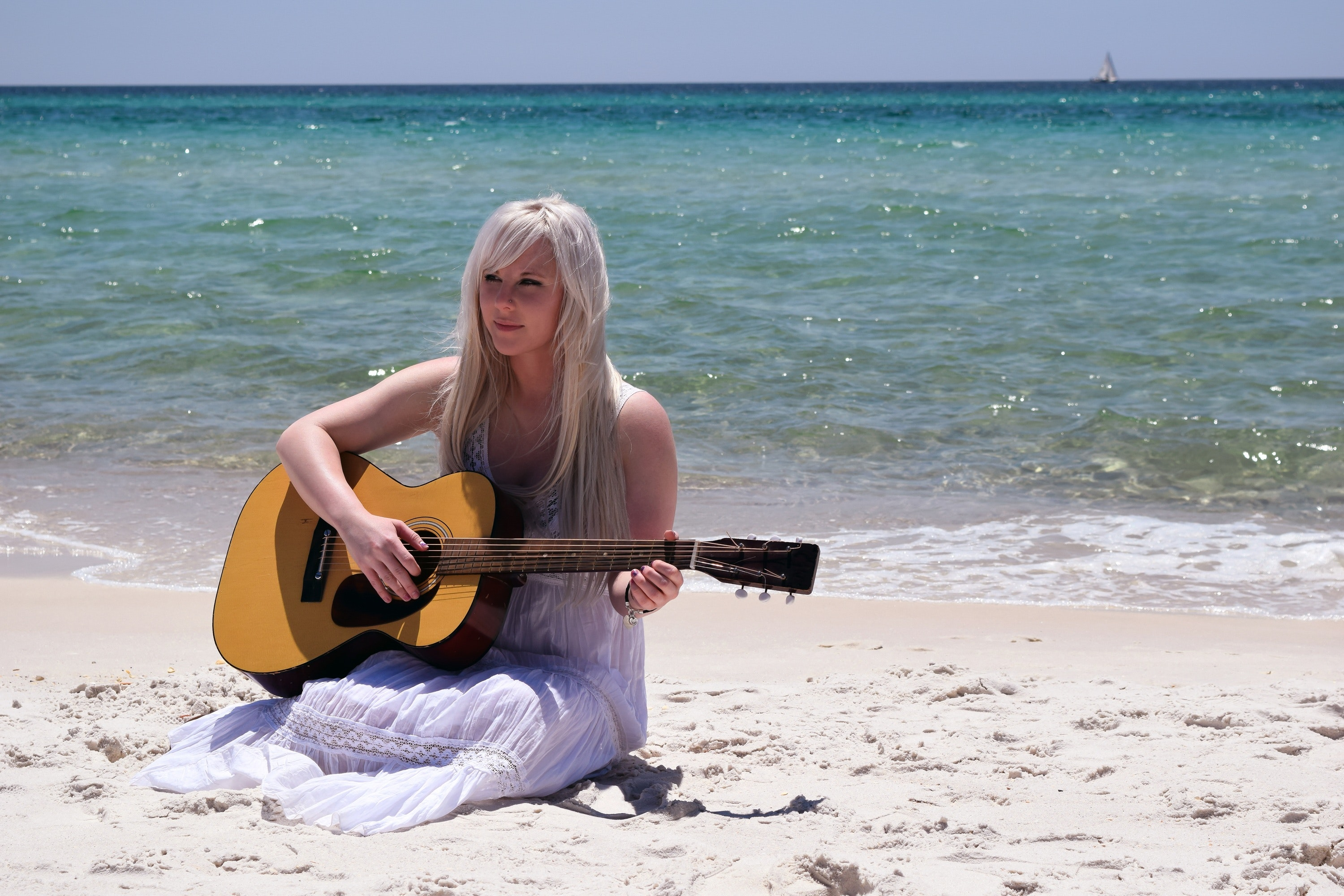 Blond woman playing spruce top dreadnought acoustic guitar by the seashore photo