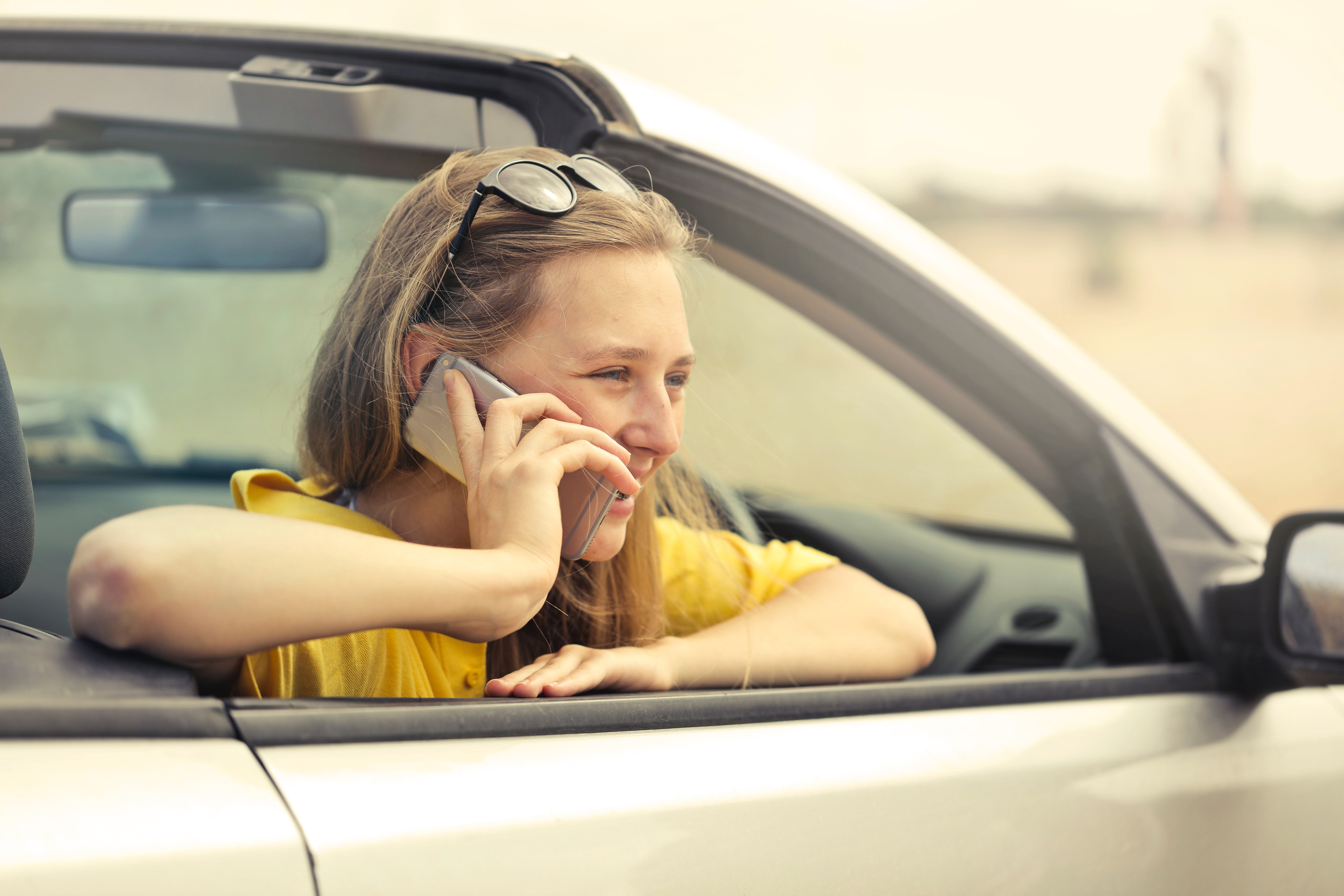 Blonde-haired Woman in Yellow T-shirt Wearing Black Sunglasses Holding Silver Smartphone, Blur, Seat, Windshield, Vehicle, HQ Photo