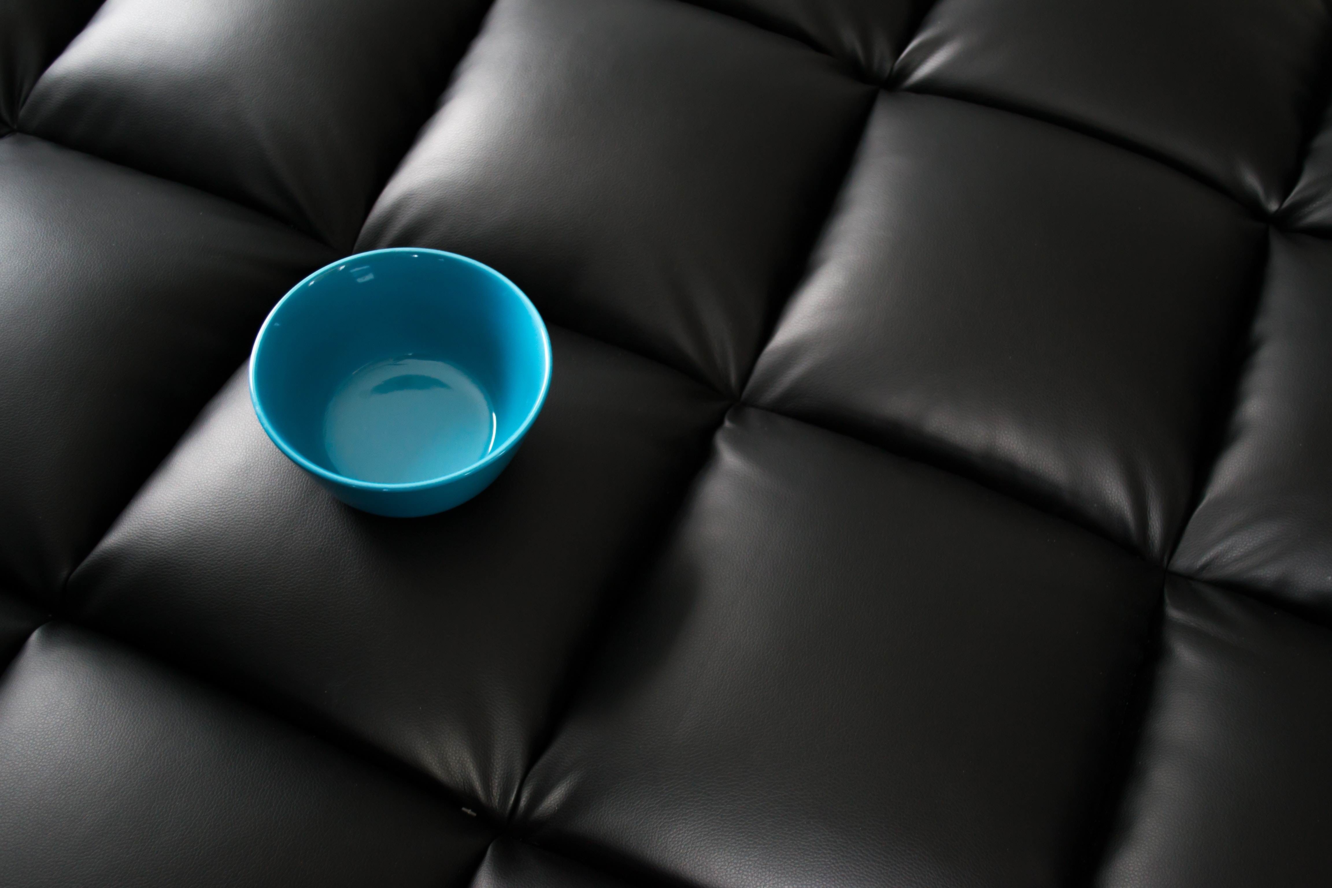 Blue ceramic bowl on black leather surface photo