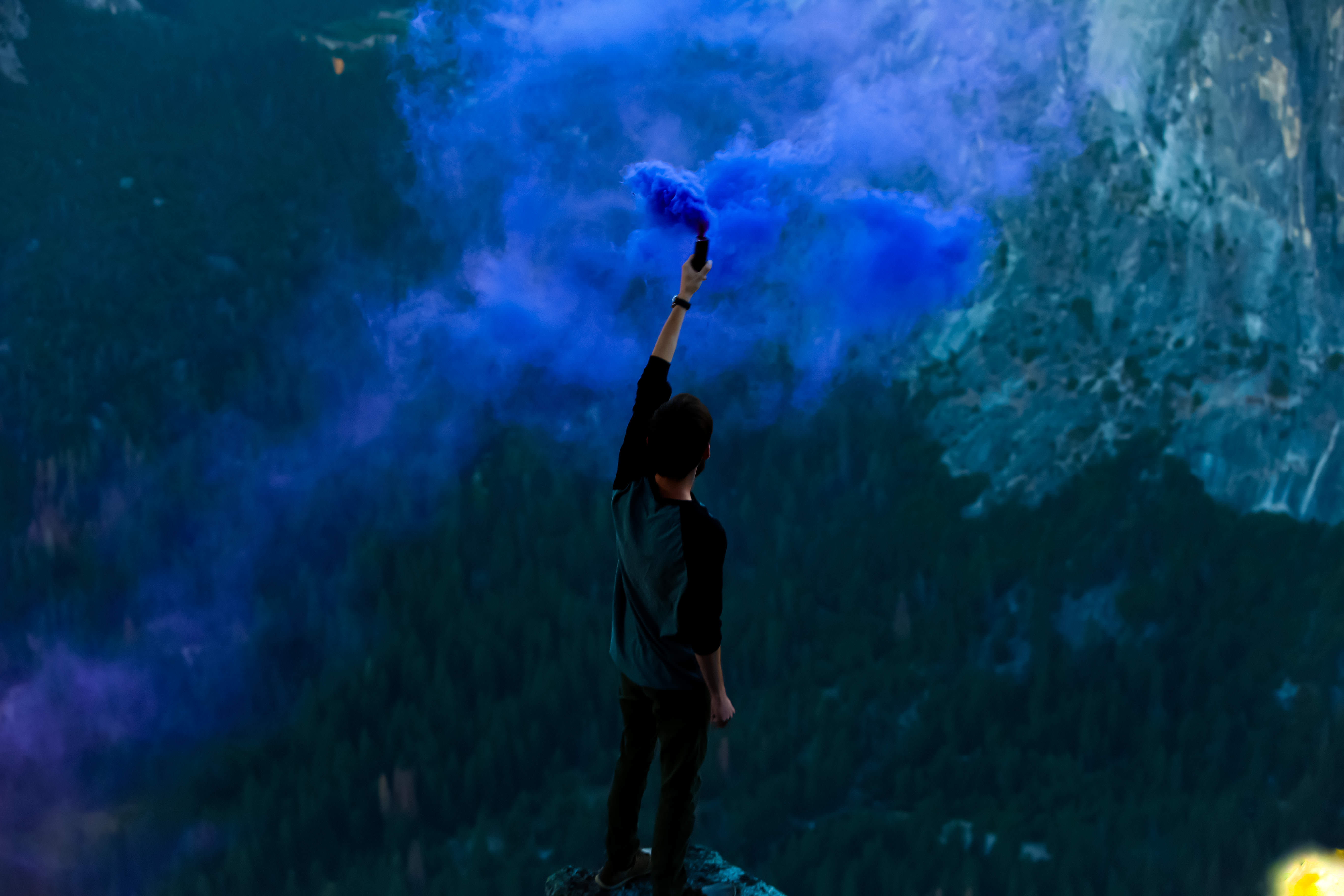 Man Holding Bottle With Blue Smoke Standing on Cliff during Daytime ...