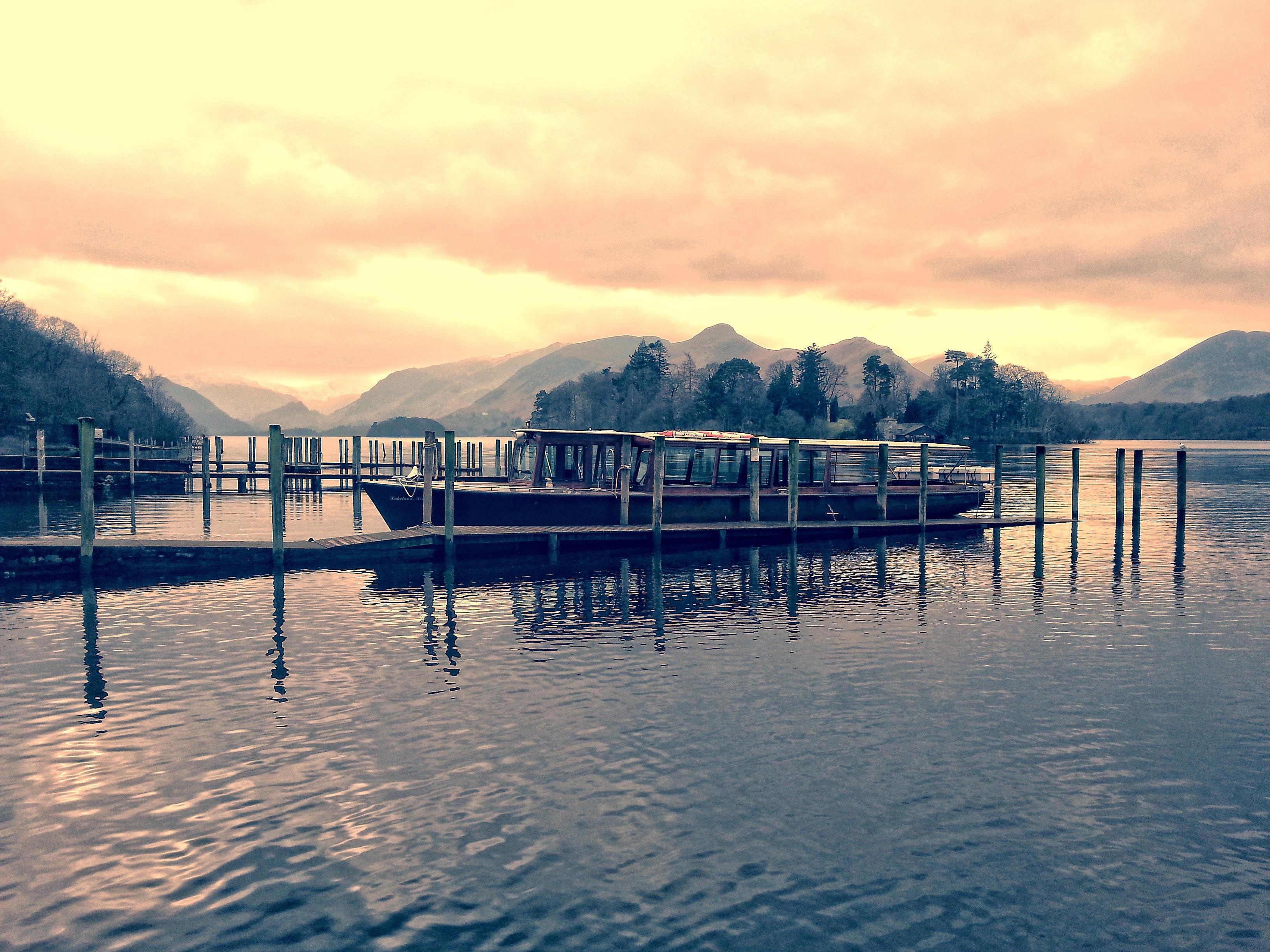 Boat beside dock during golden hour photo