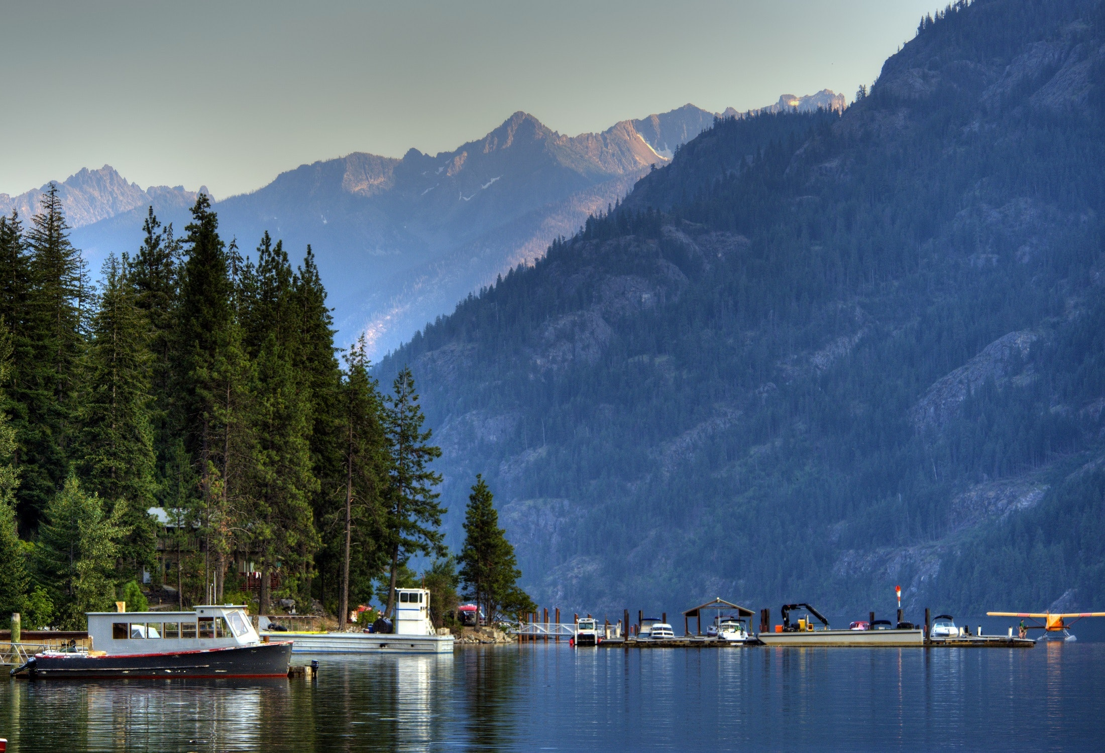 Body of Water Near Mountain Covered by Trees With Grey Clouds Above during Daytime, Boats, Dock, Forest, Lake, HQ Photo