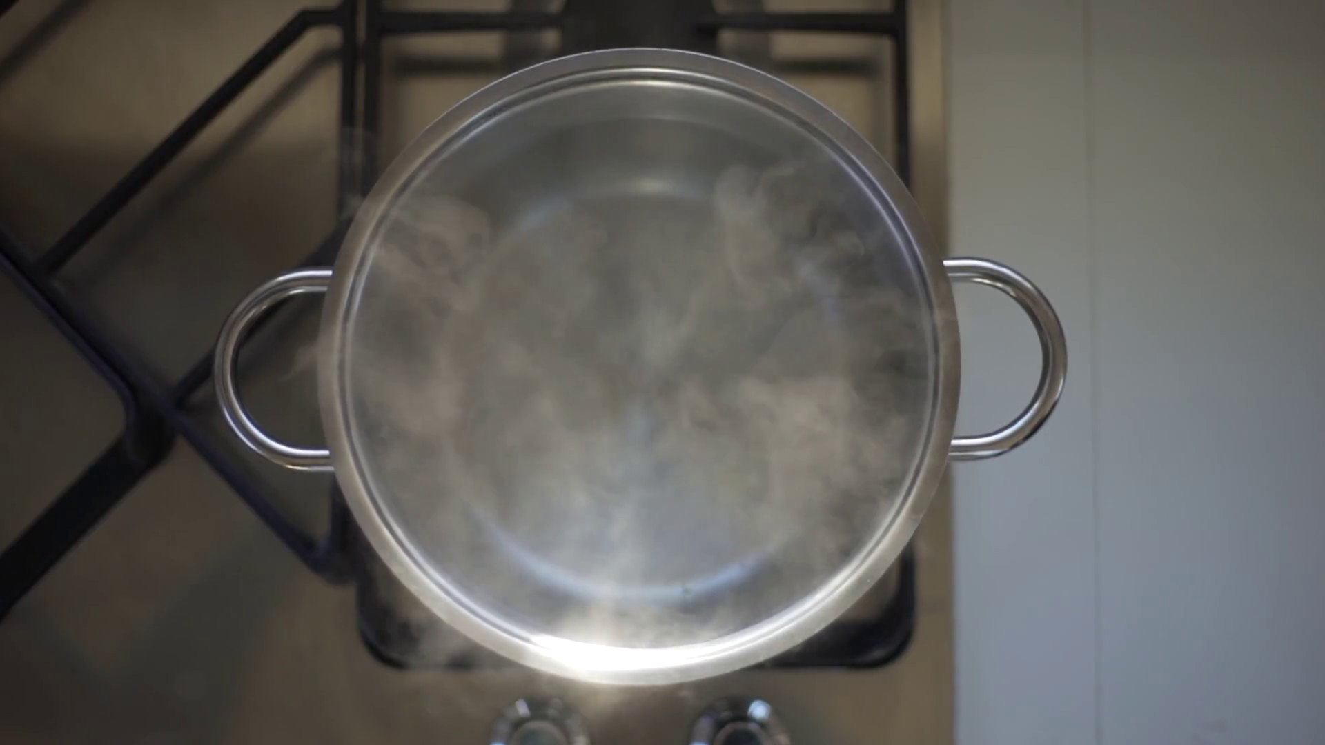 Flat lay overhead perpendicular view of boiling water on a stove in ...