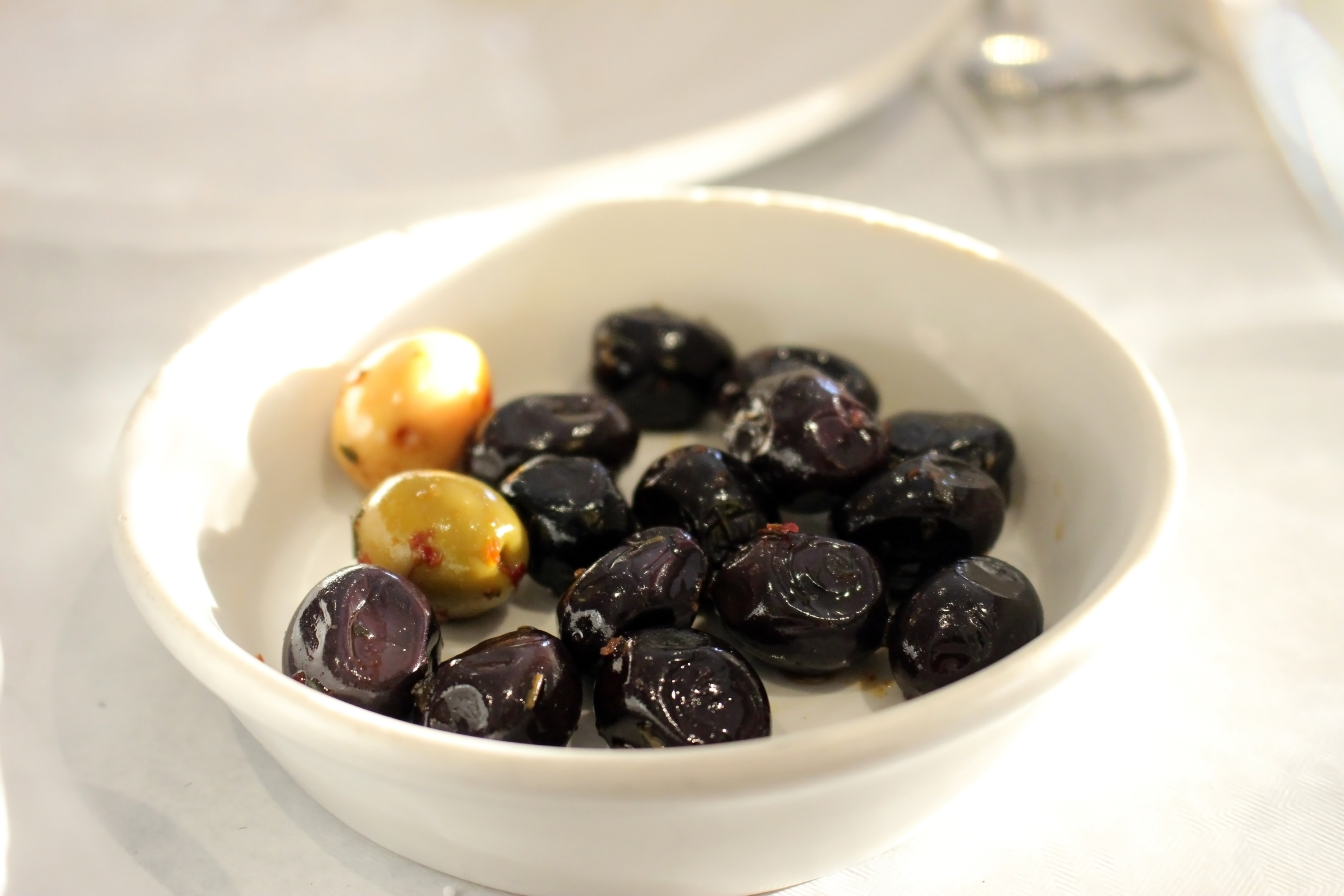 Bowl of black olives on a white table photo