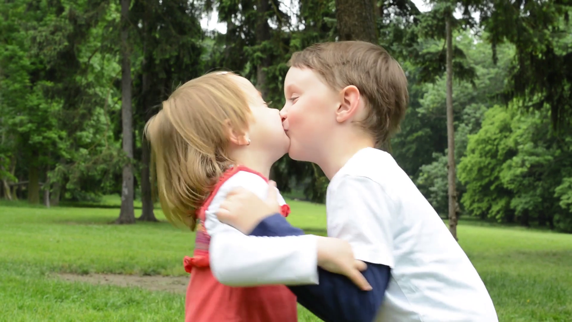 children (siblings - boy and girl) give a kiss in park Stock Video ...