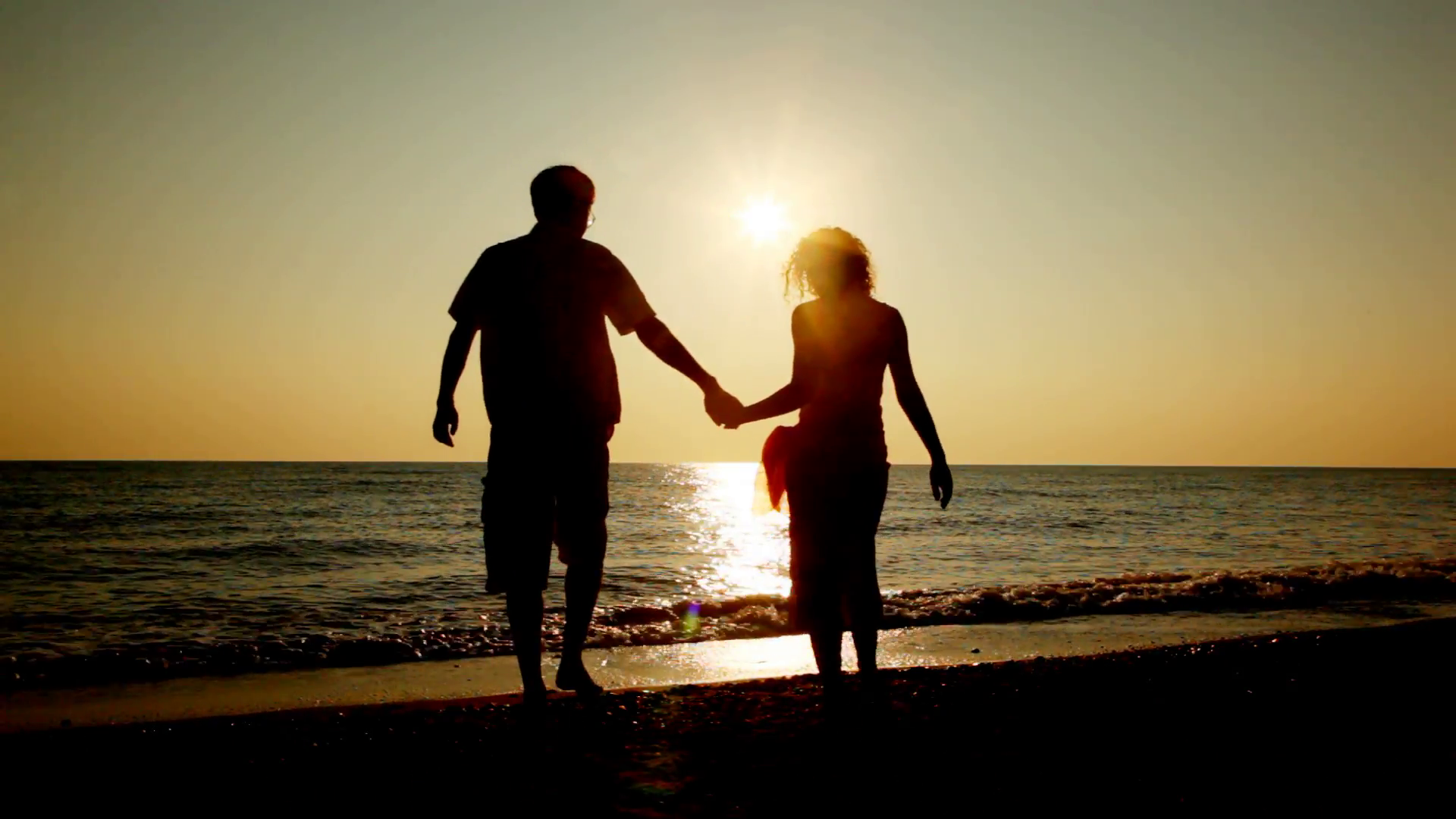 Girl and boy go at beach holding hands for sea, silhouettes on ...