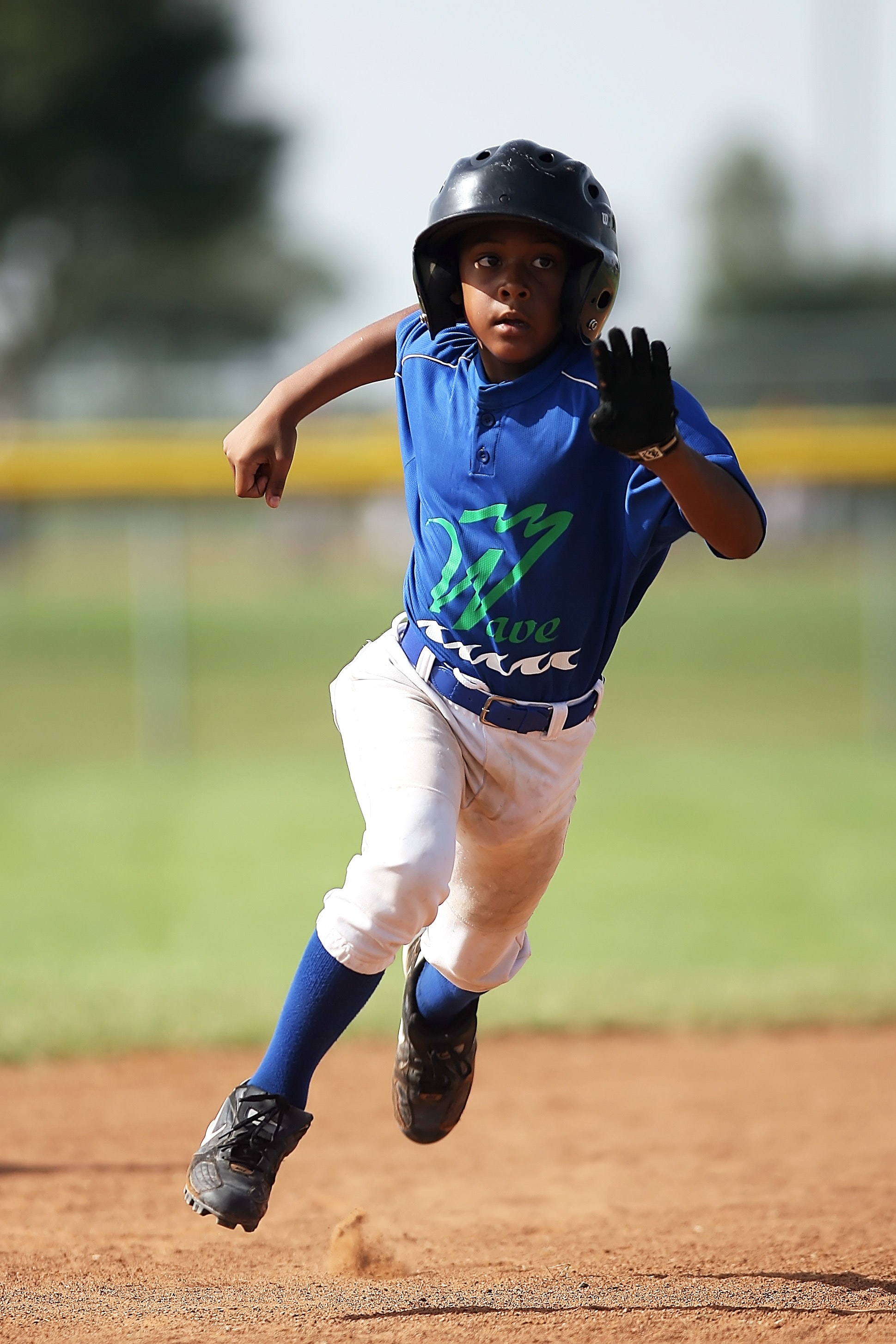 Boy in blue and white baseball jersey running on brown soil field during daytime photo