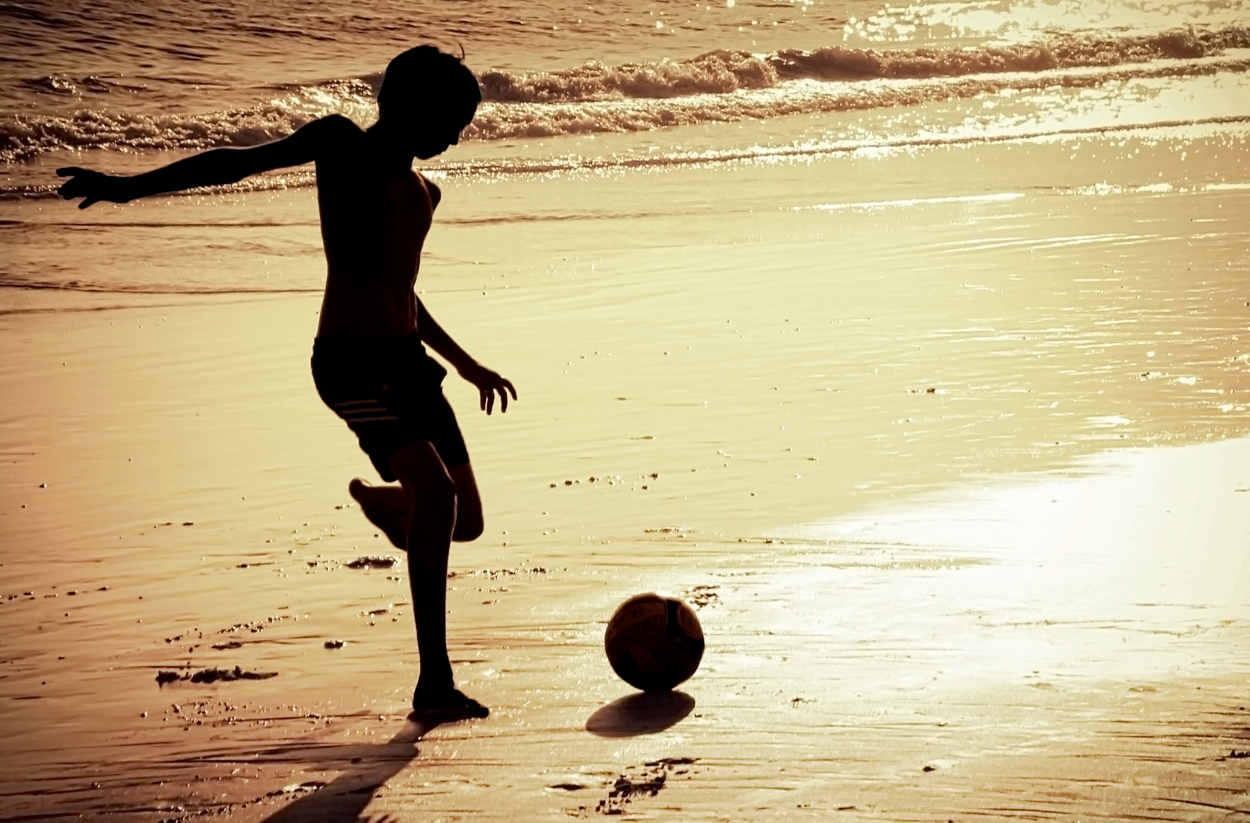 Boy on the beach playing football photo