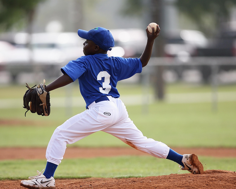 Boy wearing blue and white 3 jersey about to pitch a baseball photo