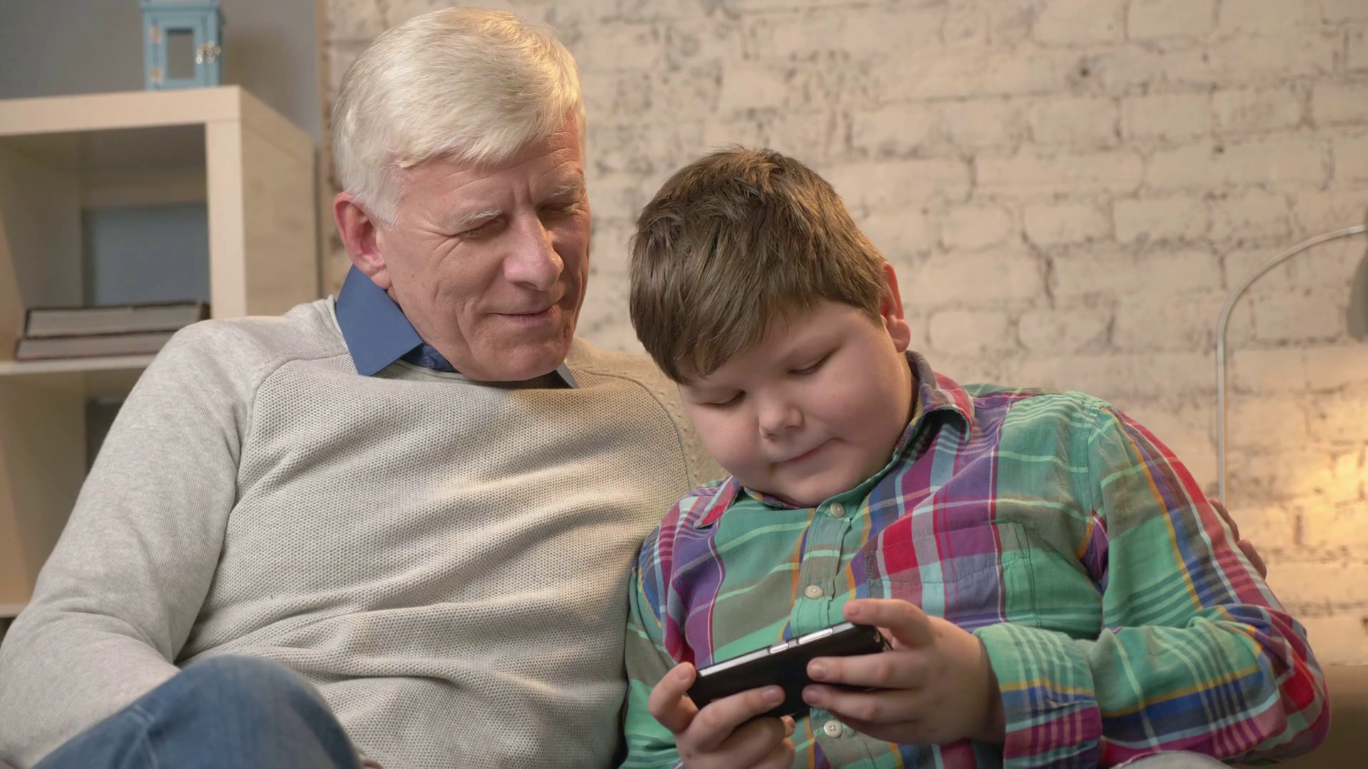 Grandfather and grandson sitting on the sofa using a smartphone ...