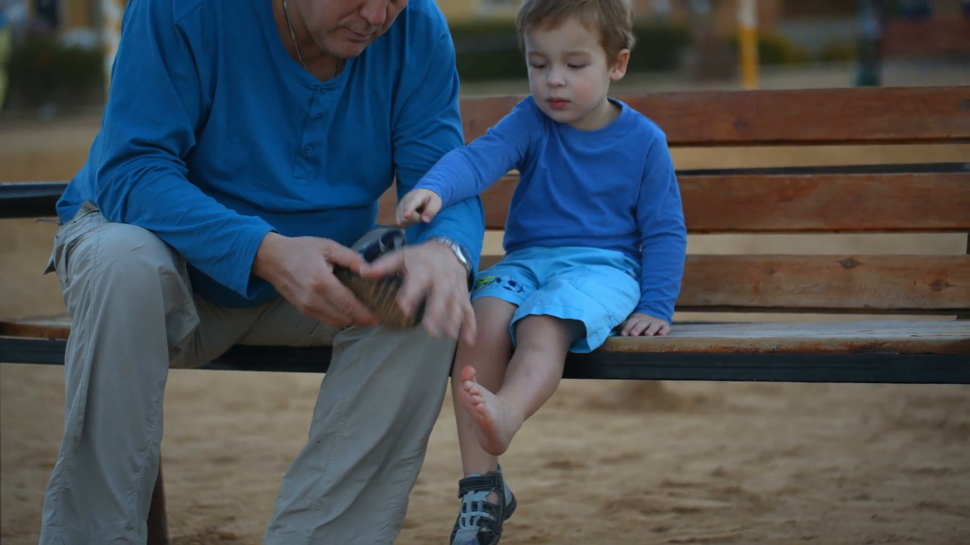 Dolly shot of a boy and his grandpa on the wooden bench. Grandfather ...