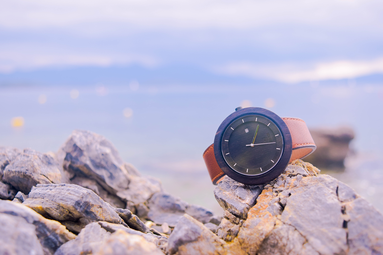 Brown and black round analog watch on beige rocks photo