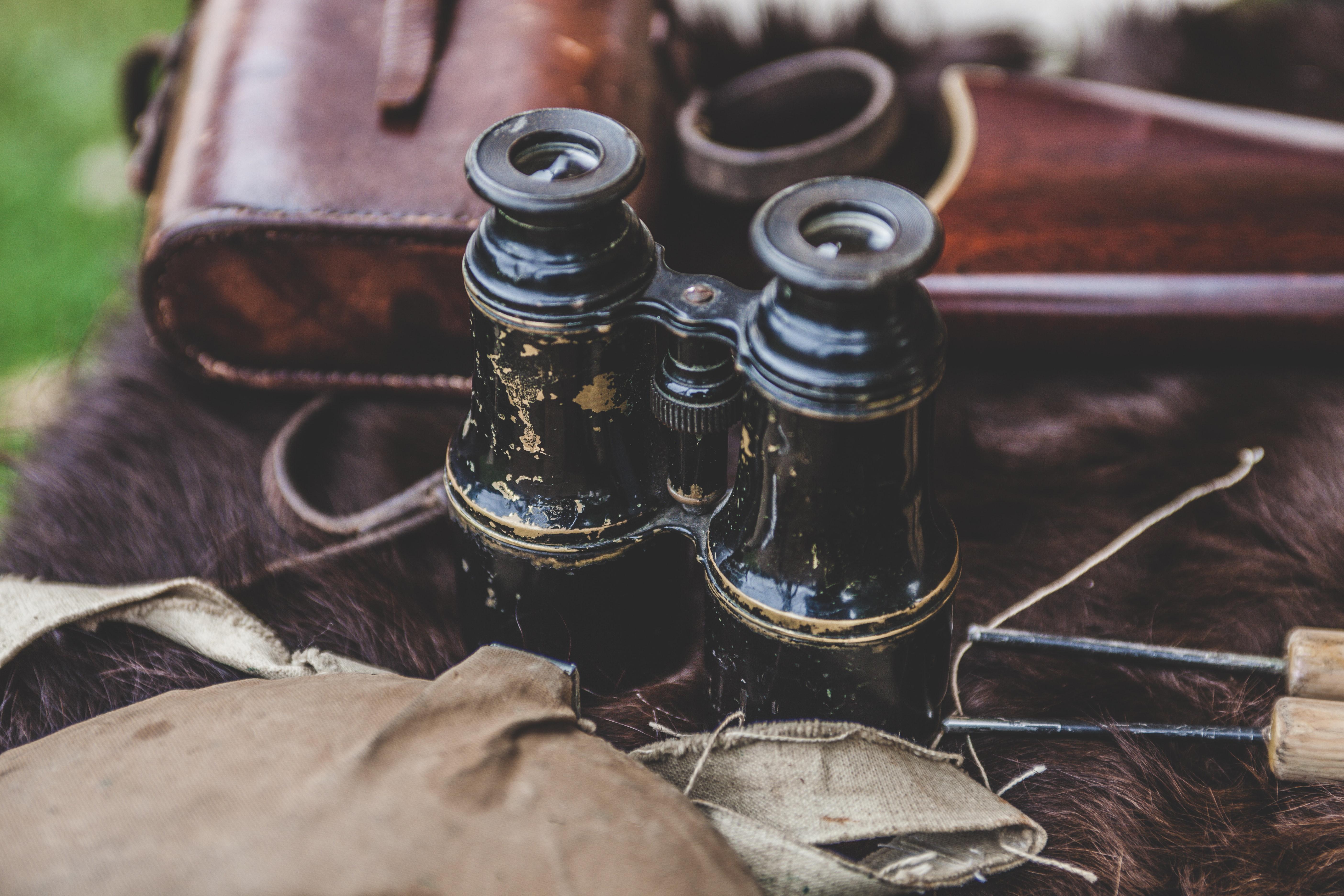 Brown binoculars on brown textile photo