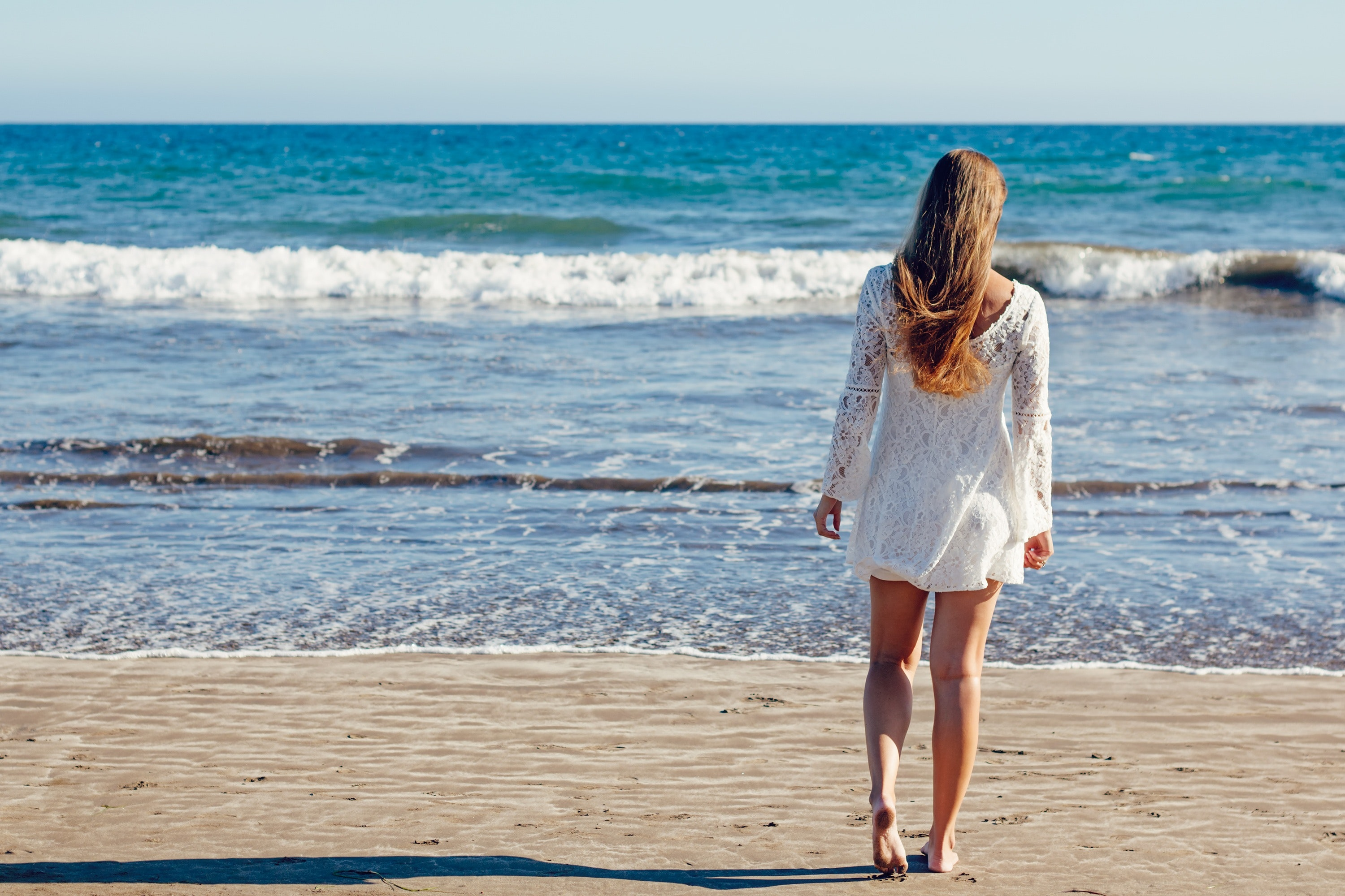 Brown haired woman in white lace long sleeve mini dress standing on seashore photo