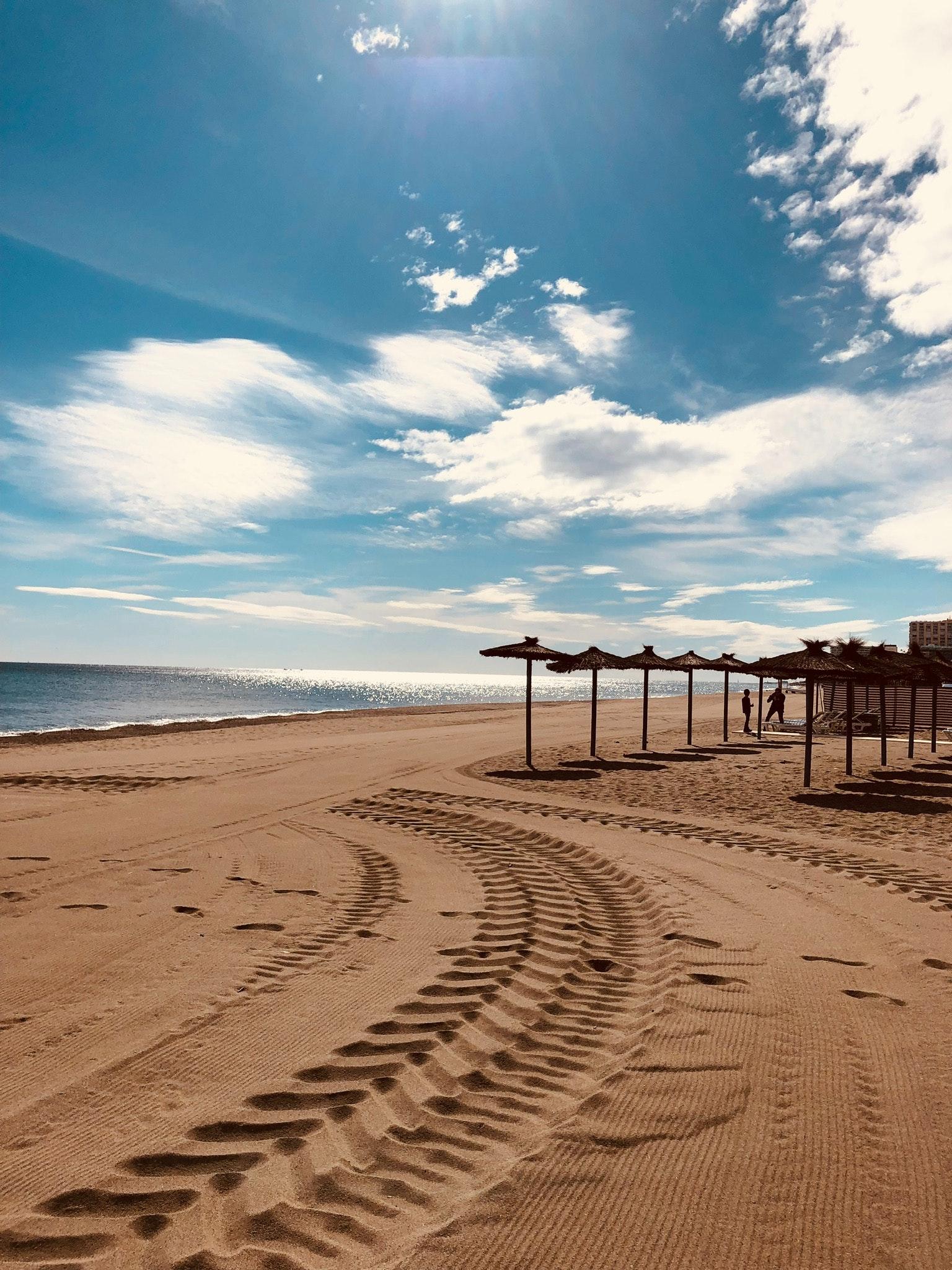 Brown sand near seashore under cloudy sky photo